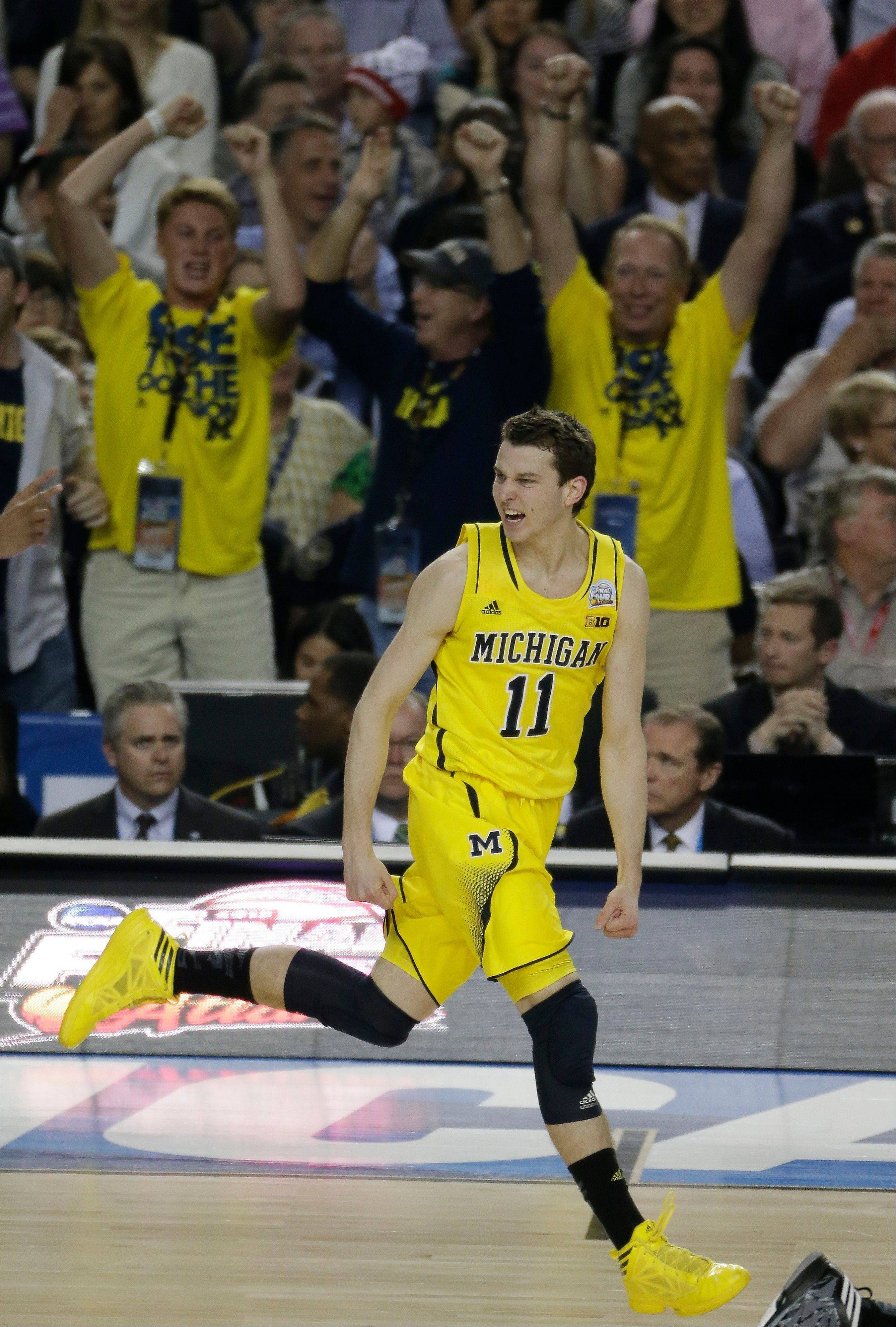 Michigan guard Nik Stauskas (11) reacts to a goal against the Louisville during the first half of the NCAA Final Four tournament college basketball championship game Monday, April 8, 2013, in Atlanta.