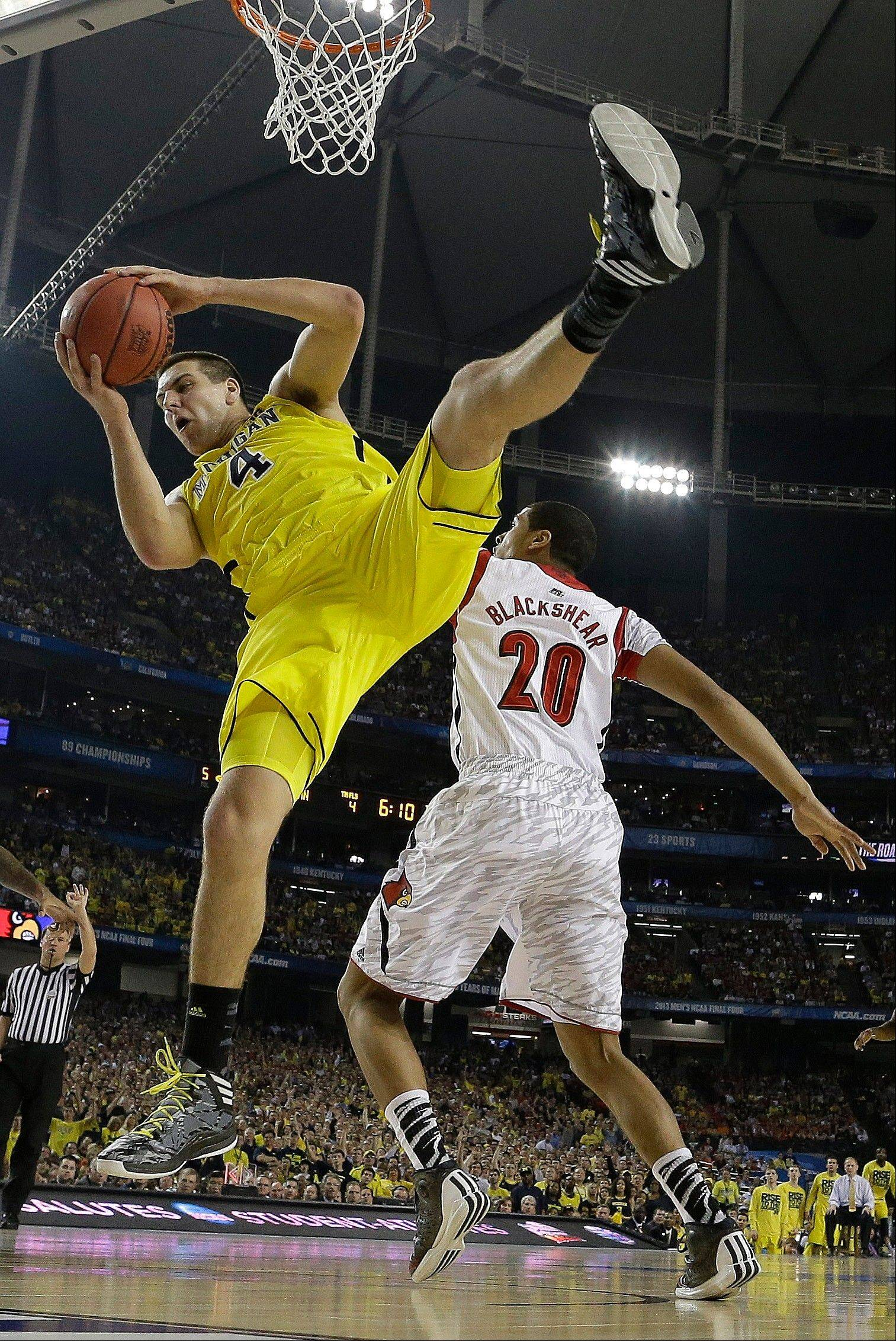 Michigan forward Mitch McGary (4) comes down with the rebound as Louisville guard/forward Wayne Blackshear (20) looks on during the first half of the NCAA Final Four tournament college basketball championship game Monday, April 8, 2013, in Atlanta.