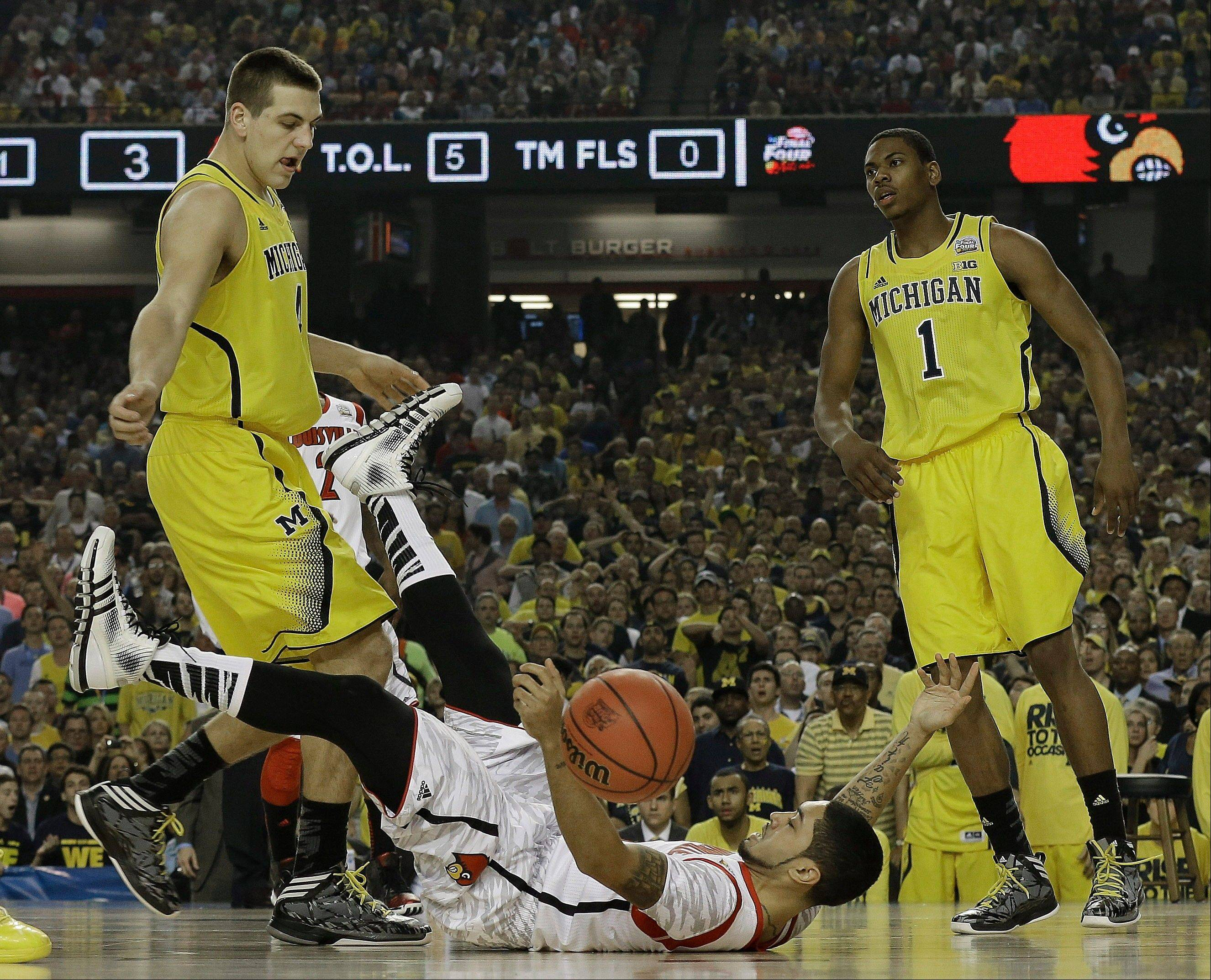 Louisville guard Peyton Siva (3) hits the court as Michigan forward Mitch McGary (4) and Michigan forward Glenn Robinson III (1) look on during the first half of the NCAA Final Four tournament college basketball championship game Monday, April 8, 2013, in Atlanta.