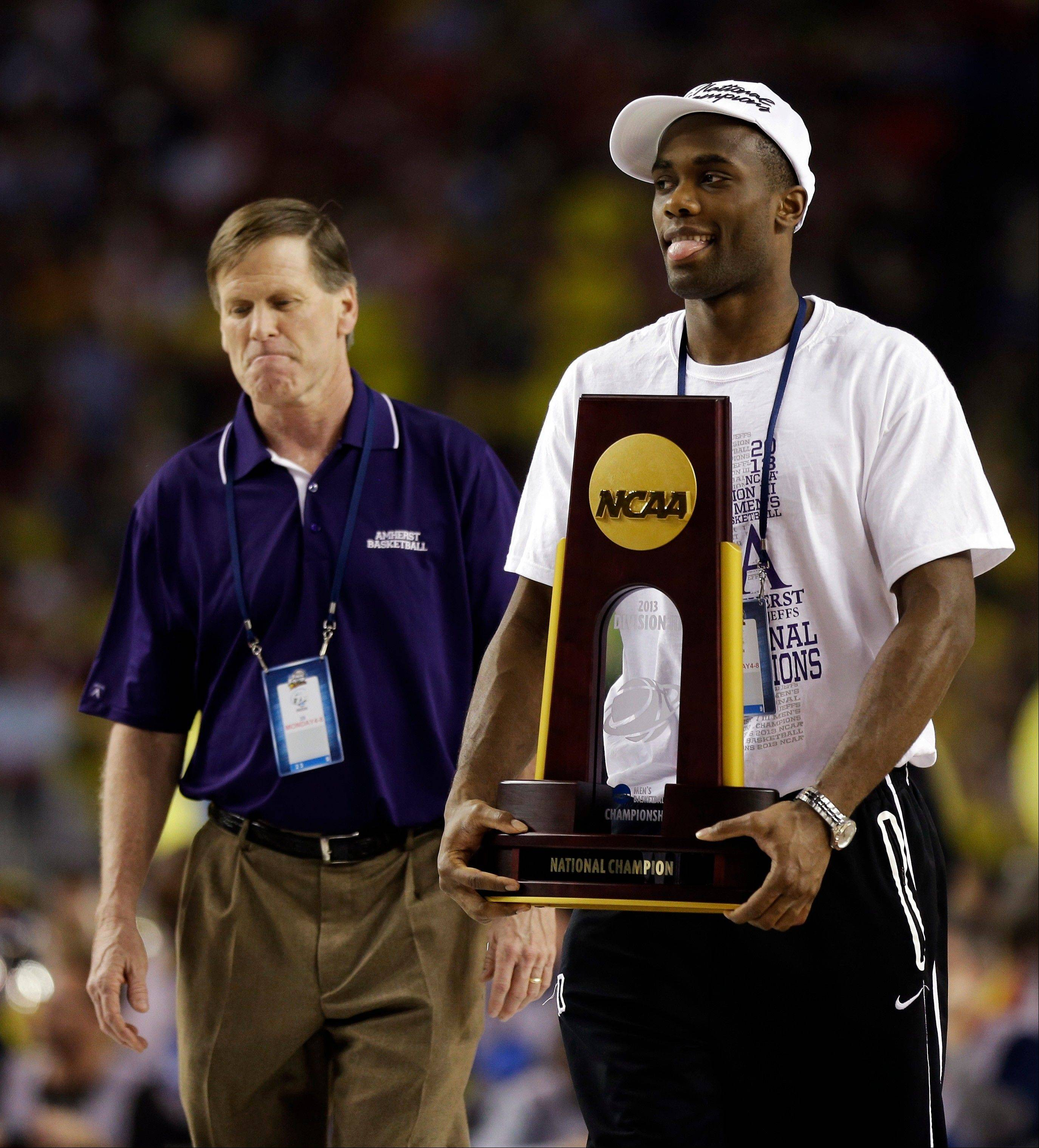 Amherst's Allen Williamson, right, carries the trophy alongside head coach David Hixon as the team is honored during halftime of the NCAA Final Four tournament college basketball championship game between Michigan and Louisville, Monday, April 8, 2013, in Atlanta. Amherst defeated Mary Hardin-Baylor 87-70 on Sunday, April 7, to win the NCAA Division III national championship college basketball game.