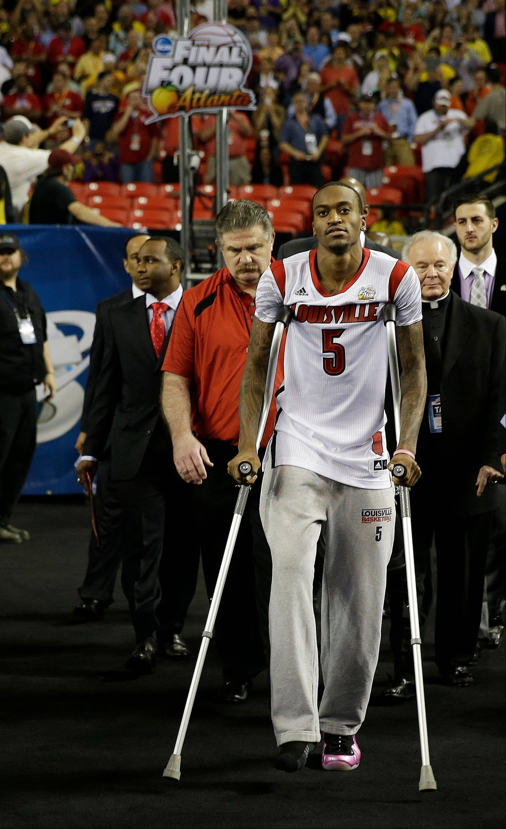Louisville guard Kevin Ware walks out to the court before the first half of the NCAA Final Four tournament college basketball championship game against the Michigan, Monday, April 8, 2013, in Atlanta.