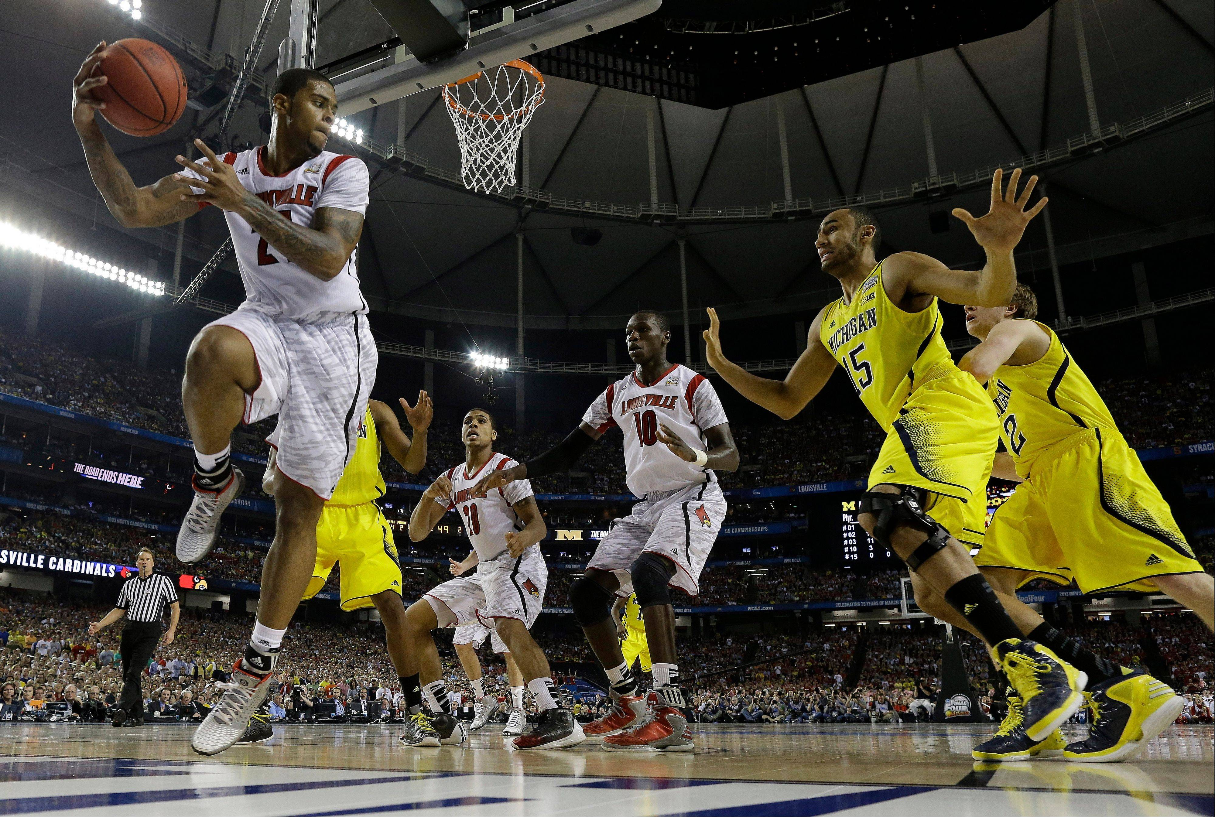 Louisville forward Chane Behanan (21) grabs a rebound as Michigan forward Jon Horford (15) looks on during the second half of the NCAA Final Four tournament college basketball championship game Monday, April 8, 2013, in Atlanta.