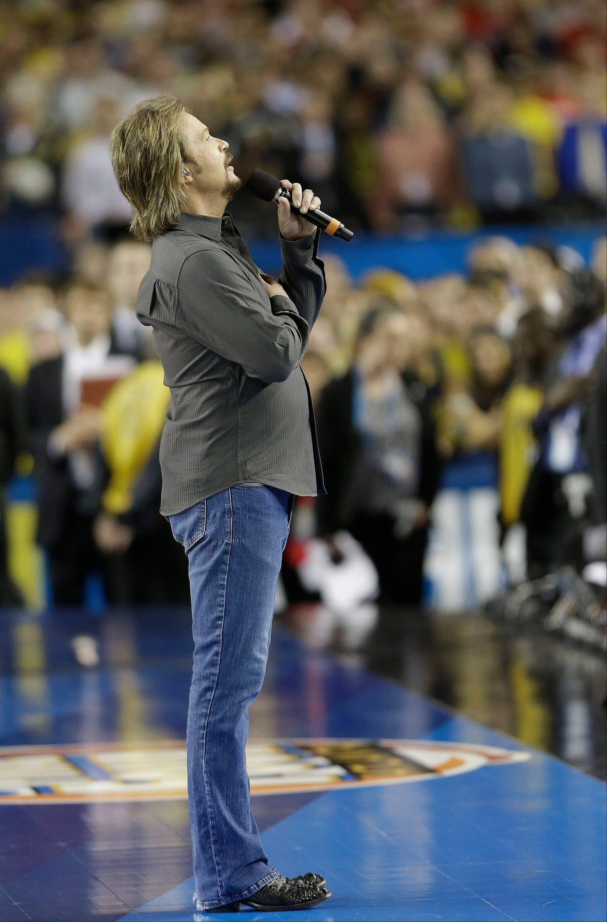 Singer Travis Tritt sings the national anthem before the first half of the NCAA Final Four tournament college basketball championship game between Michigan and Louisville, Monday, April 8, 2013, in Atlanta.