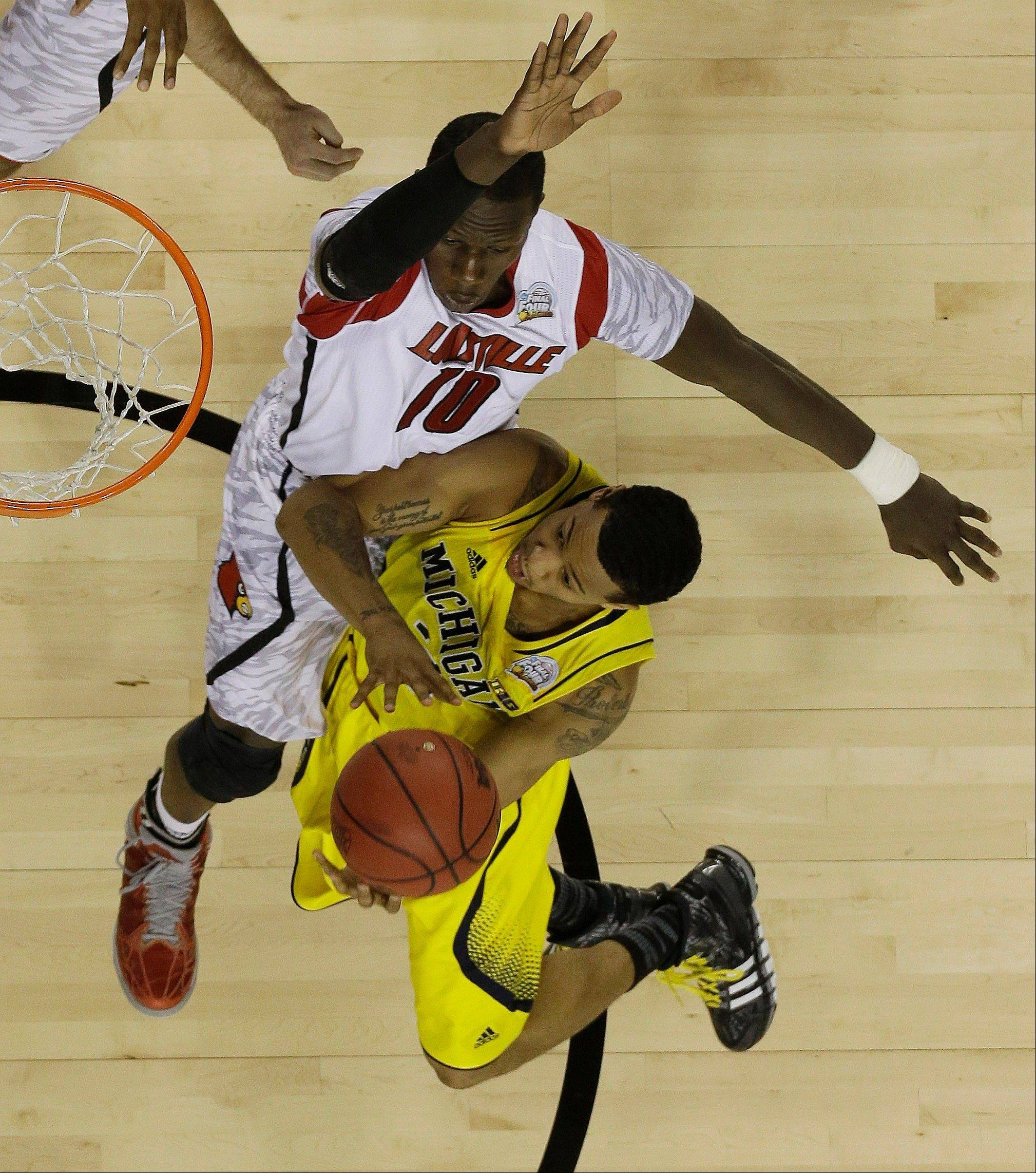 Michigan guard Trey Burke (3) heads to the hoop as Louisville center Gorgui Dieng (10) defends during the second half of the NCAA Final Four tournament college basketball championship game Monday, April 8, 2013, in Atlanta.