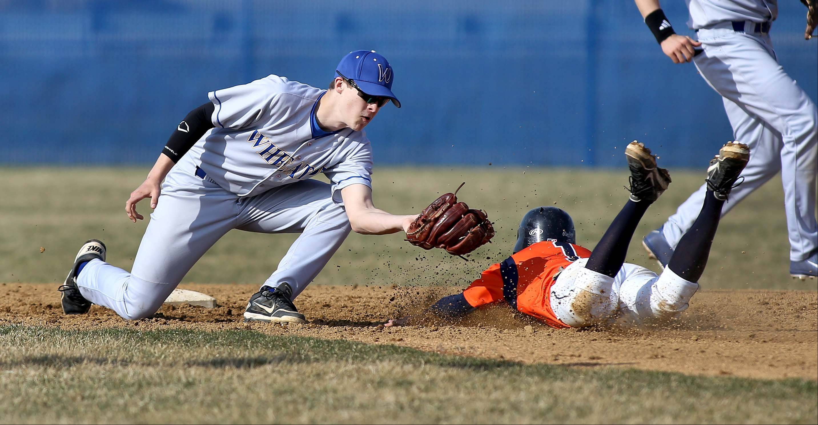 River Williams of Wheaton North tags out Ryan Krainz of Naperville North at second base in the first inning during baseball on Monday in Naperville.