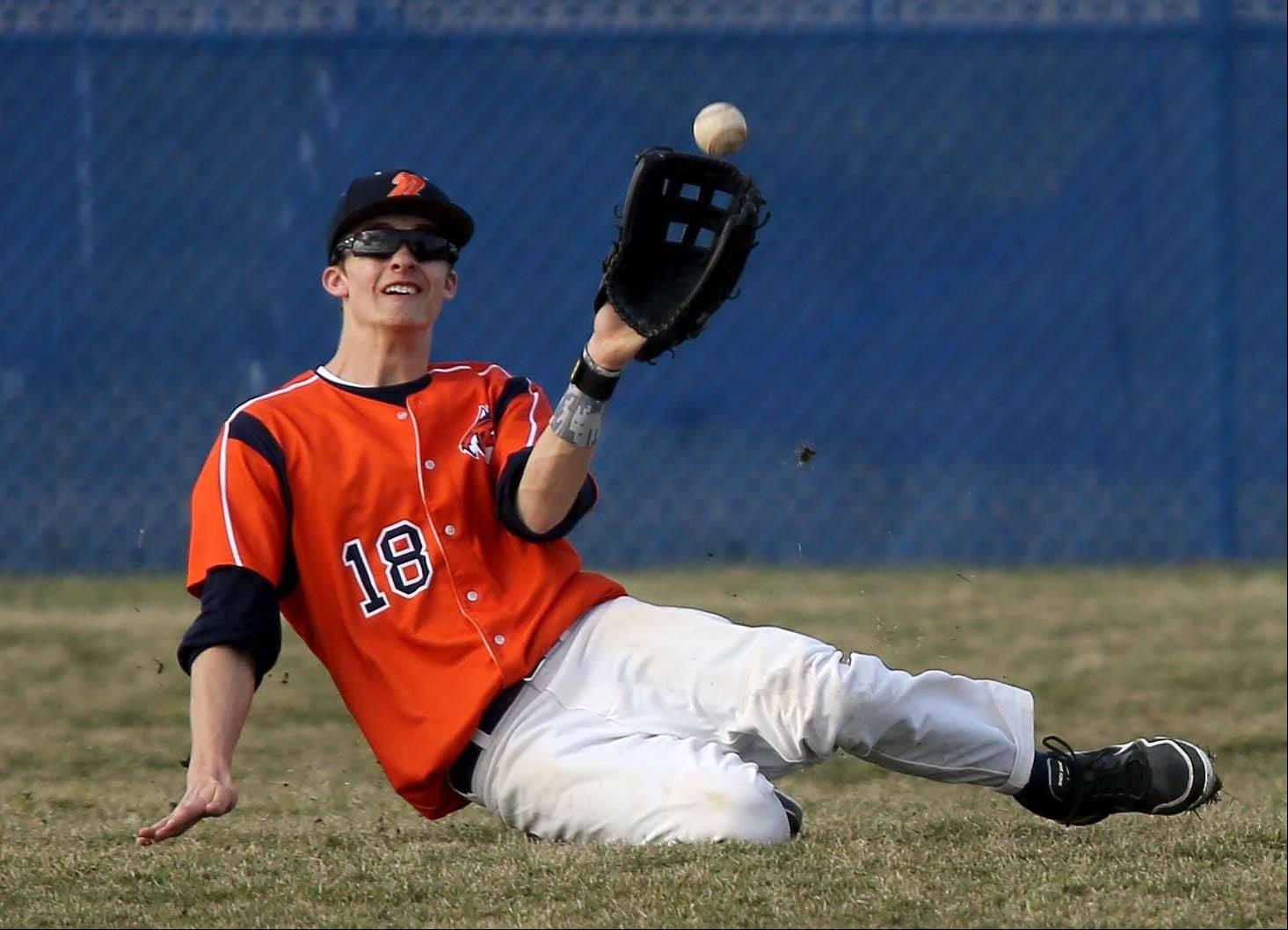 Alex Garon of Naperville North makes a sliding catch in the outfield during the third inning of baseball against Wheaton North on Monday in Naperville.