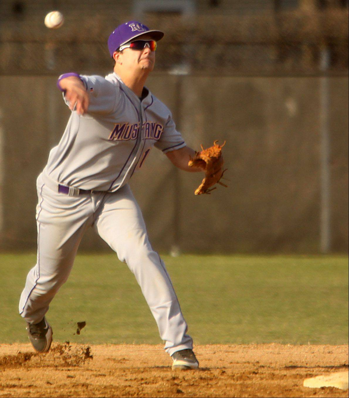 Rolling Meadows' Mickey Wazorick tosses to first base for a putout at Hersey on Monday night.