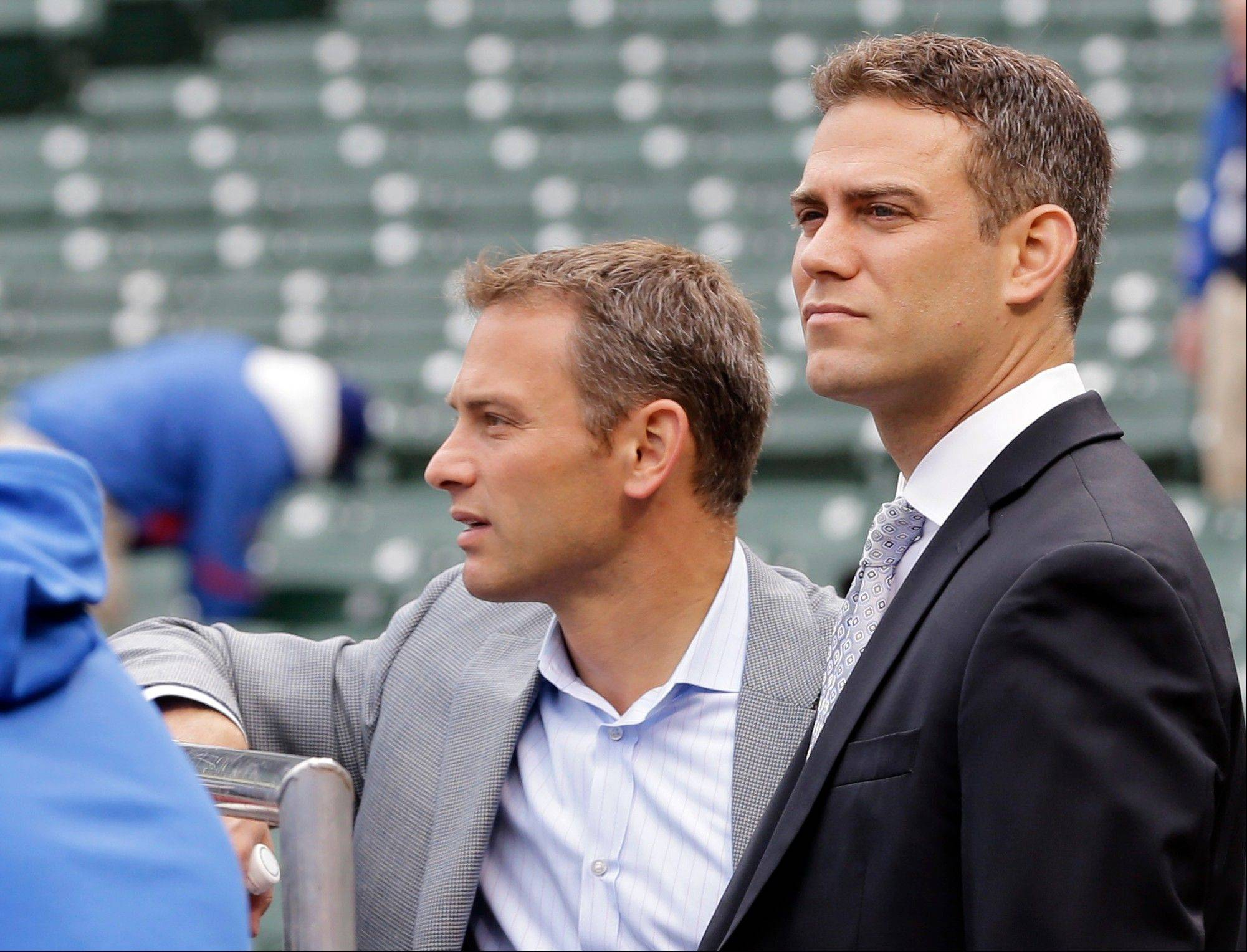 Cubs President of Baseball Operations Theo Epstein, right, and general manager Jed Hoyer watch the team's batting practice before Monday's home-opener at Wrigley Field.