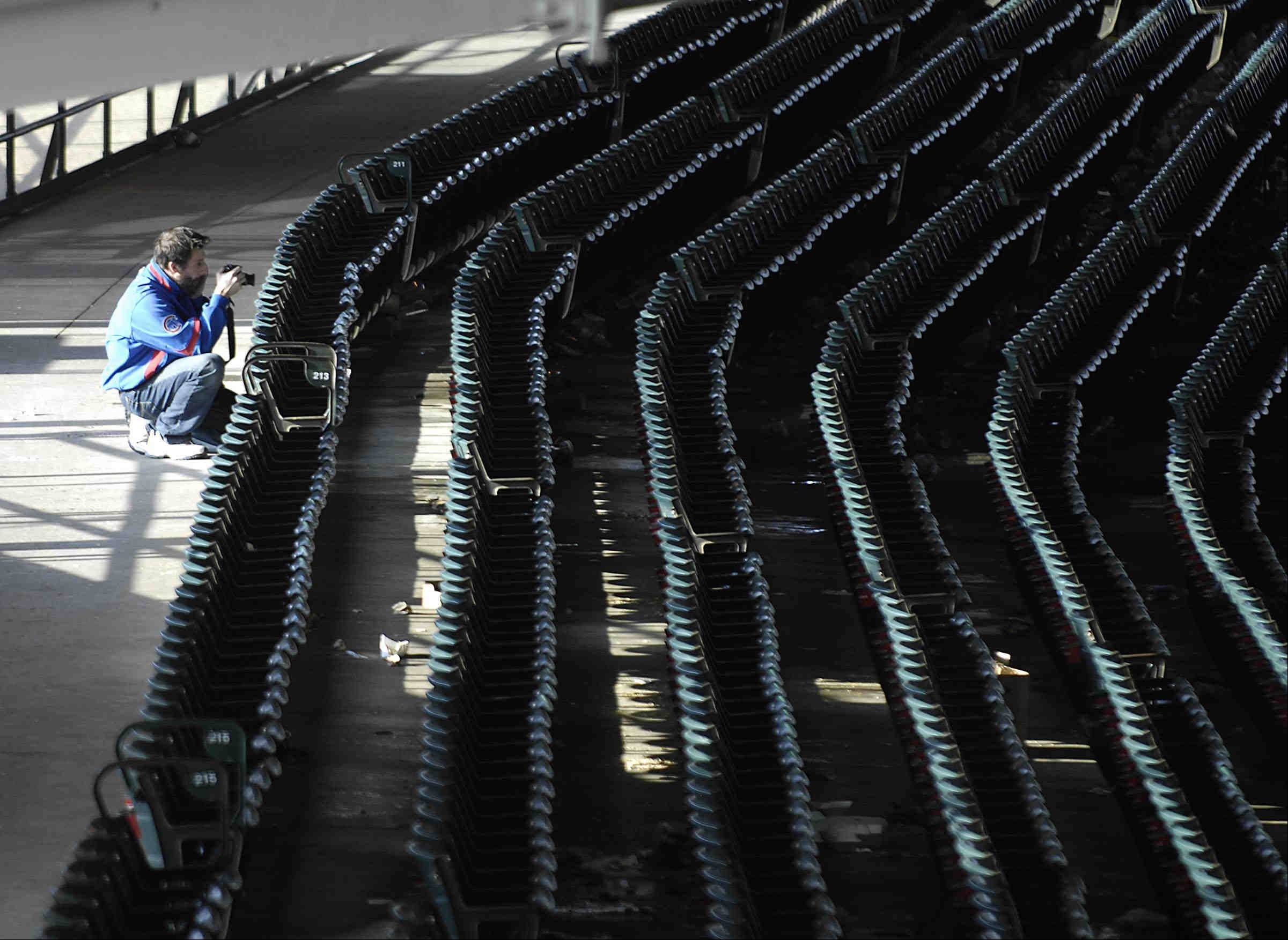 A Cubs fan takes photos of an empty Wrigley Field after Monday's loss to Milwaukee.