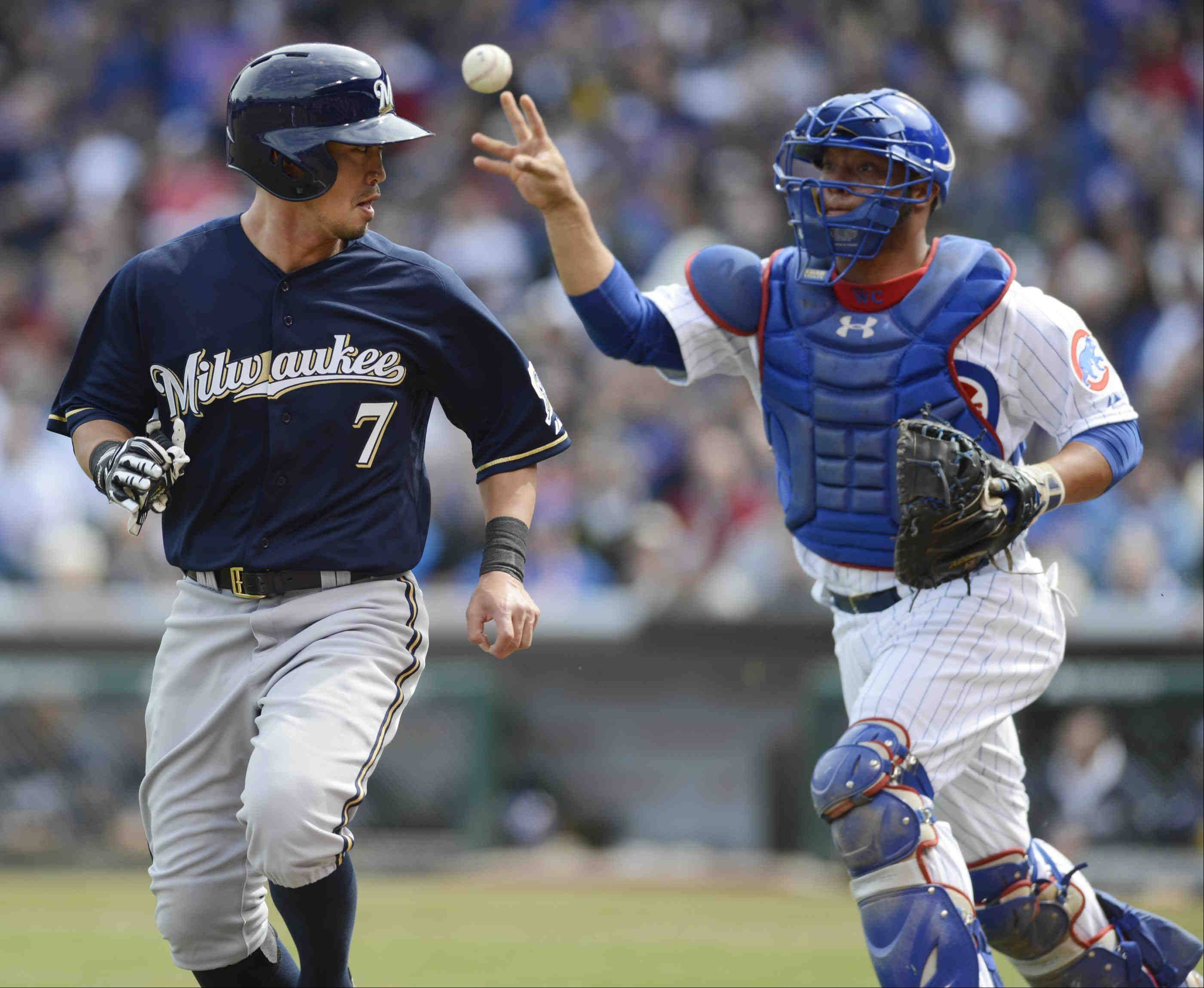 Cubs catcher Welington Castillo tosses the ball to teammate third baseman Luis Valbuena to tag out Milwaukee Brewers' Milwaukee Brewers right fielder Norichika Aoki at Monday's Wrigley Field home-opener. Aoki was trying to score from third on a hit by Ricky Weeks.