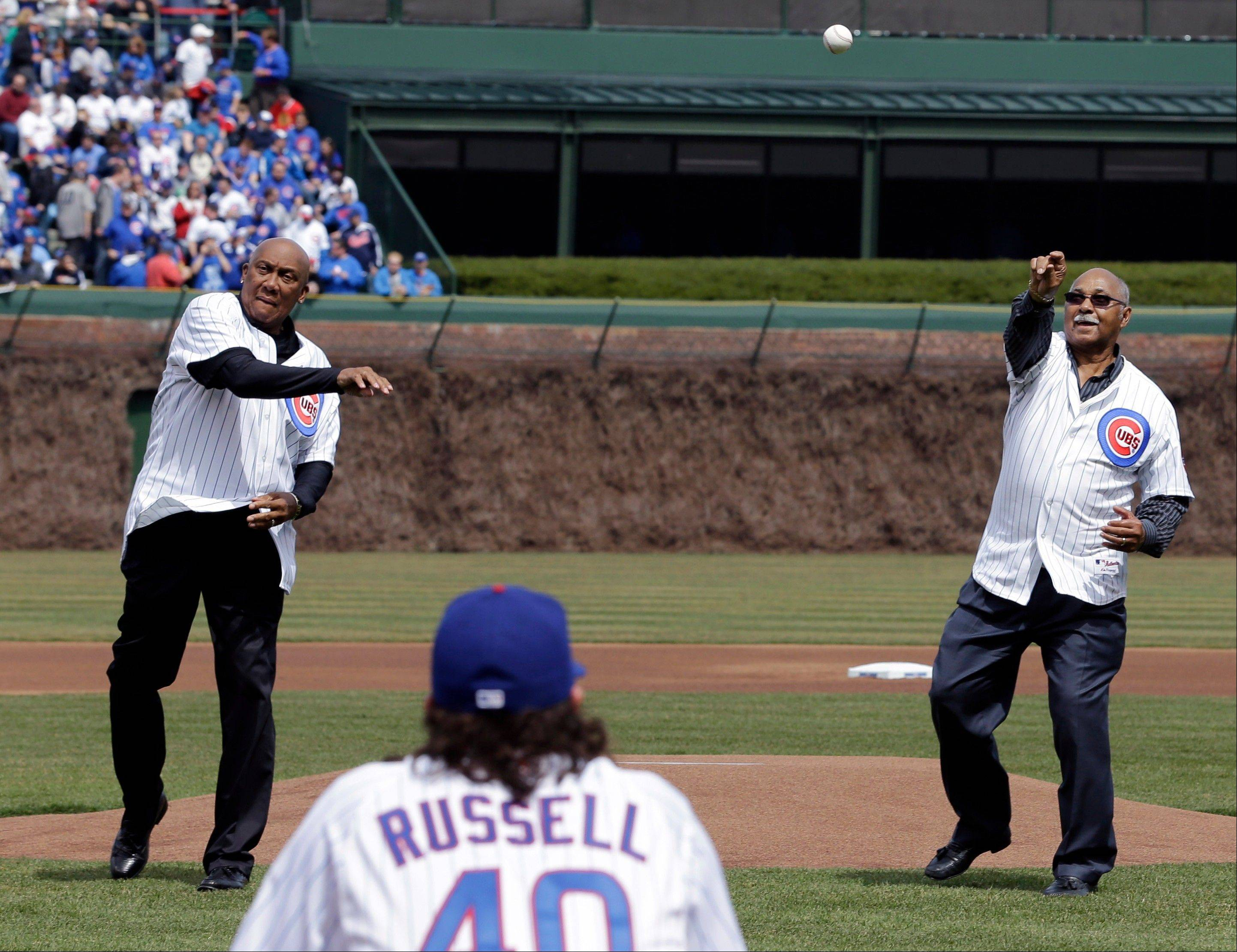 Former baseball players Ferguson Jenkins, left, and Billy Williams throw out the opening pitch for the Chicago Cubs' home opener against the Milwaukee Brewers in Chicago, Monday, April 8, 2013.