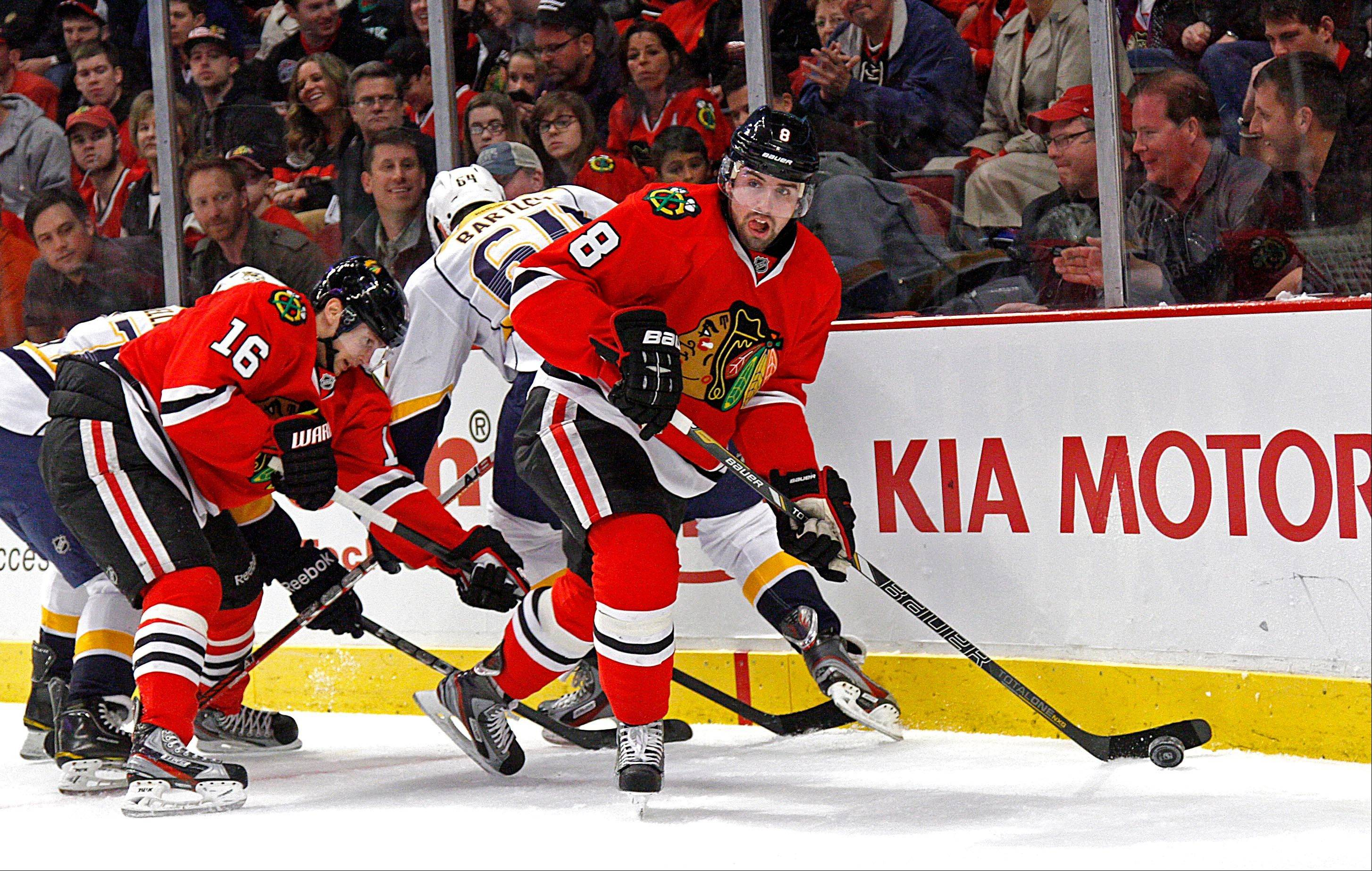 Blackhawks coach Joel Quenneville liked what he saw Sunday from defenseman Nick Leddy, here carrying the puck away from a host of players in the win.