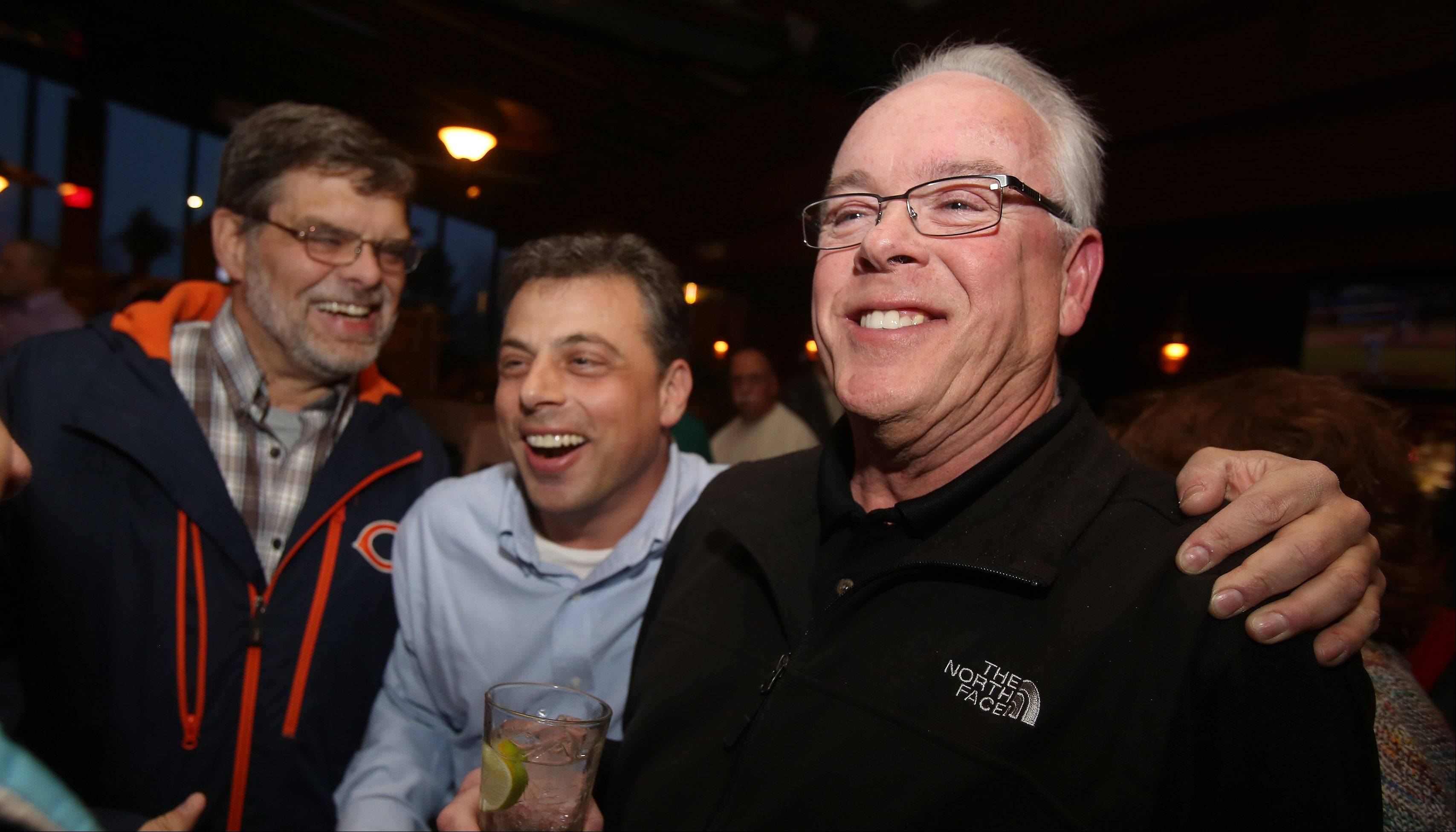 Lake Zurich village president candidate Tom Poynton, right, is congratulated by trustee candidate Jeff Halen as they watch election results come in during his election party Tuesday at Beelow�s Steakhouse. Poynton and Halen both won.
