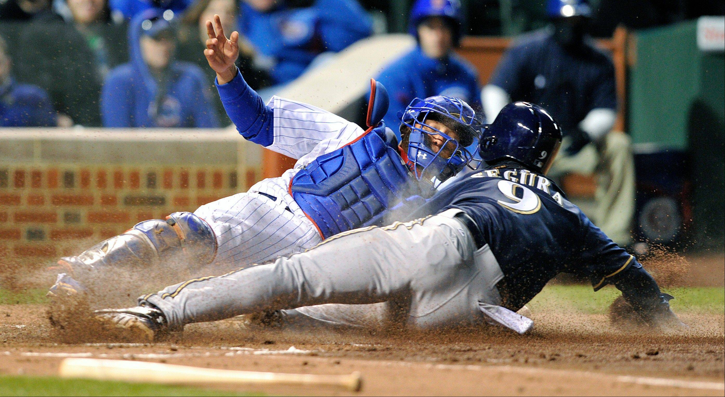 Welington Castillo misses the tag on the Milwaukee Brewers' Jean Segura (9) as Segura scores on a ball hit by Norichika Aoki during the second inning Tuesday, April 9, 2013, in Chicago.