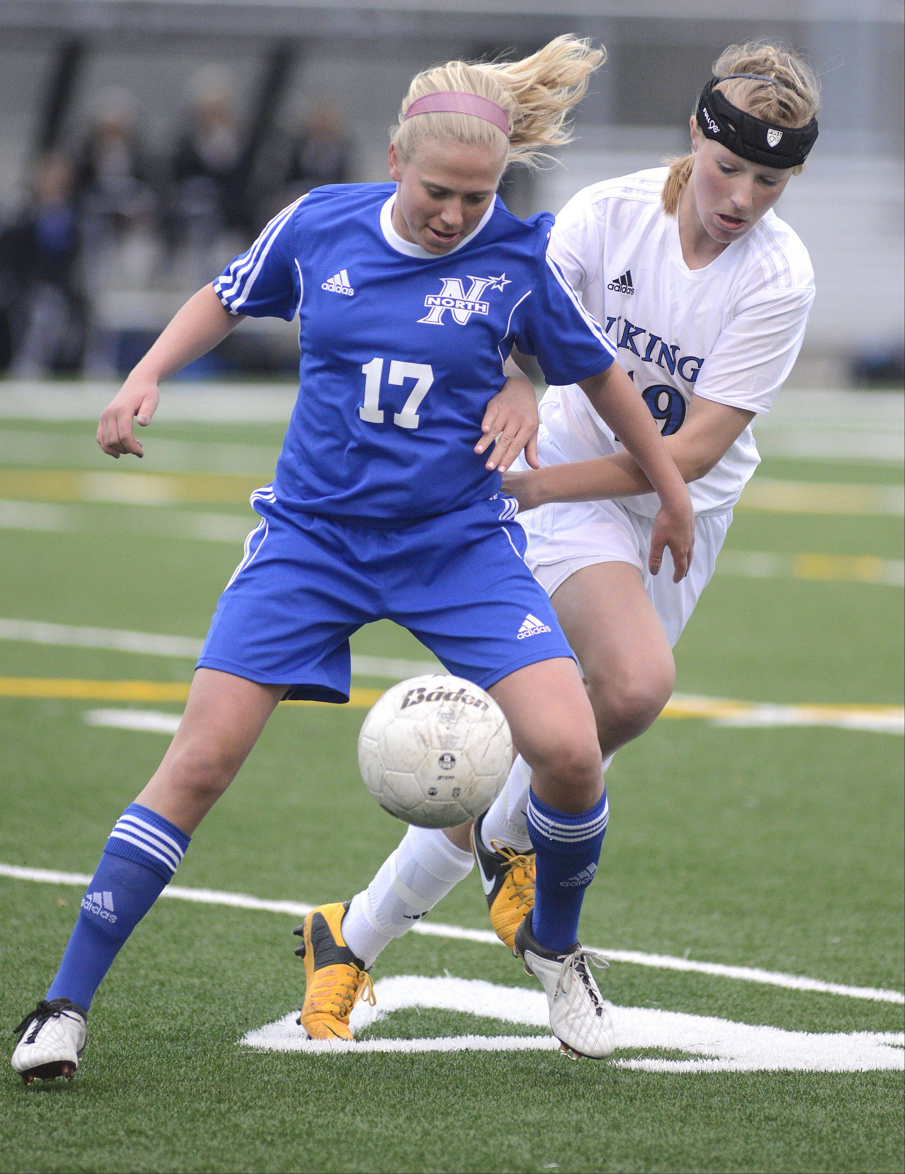 St. Charles North�s Kelly Manski and Geneva�s Megan Kozlow battle for the ball in the first half on Tuesday, April 9.