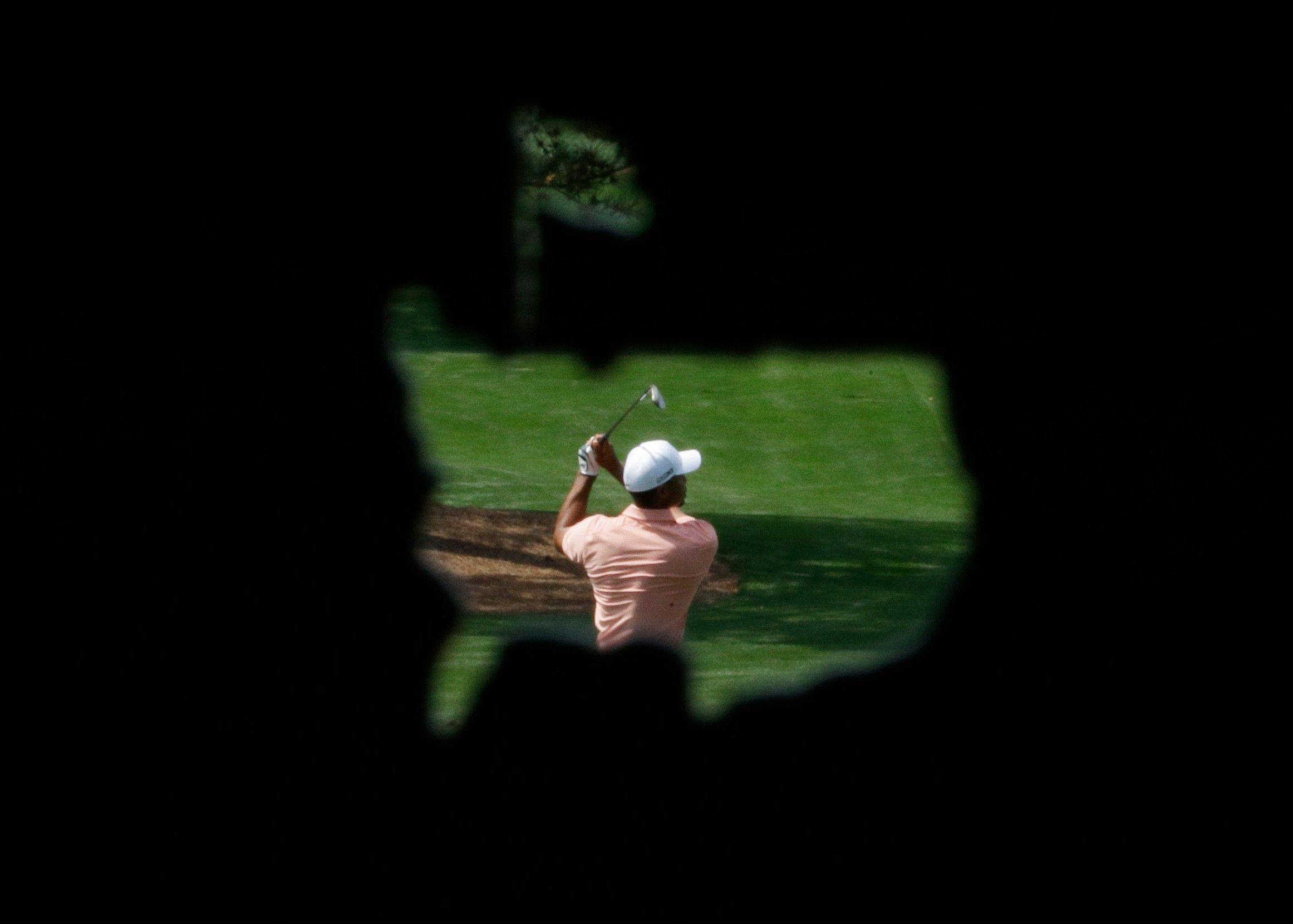 In a photo taken through a metal cutout of the Masters' logo, Tiger Woods hits on the driving range during a practice round for the Masters golf tournament Tuesday, April 9, 2013, in Augusta, Ga.