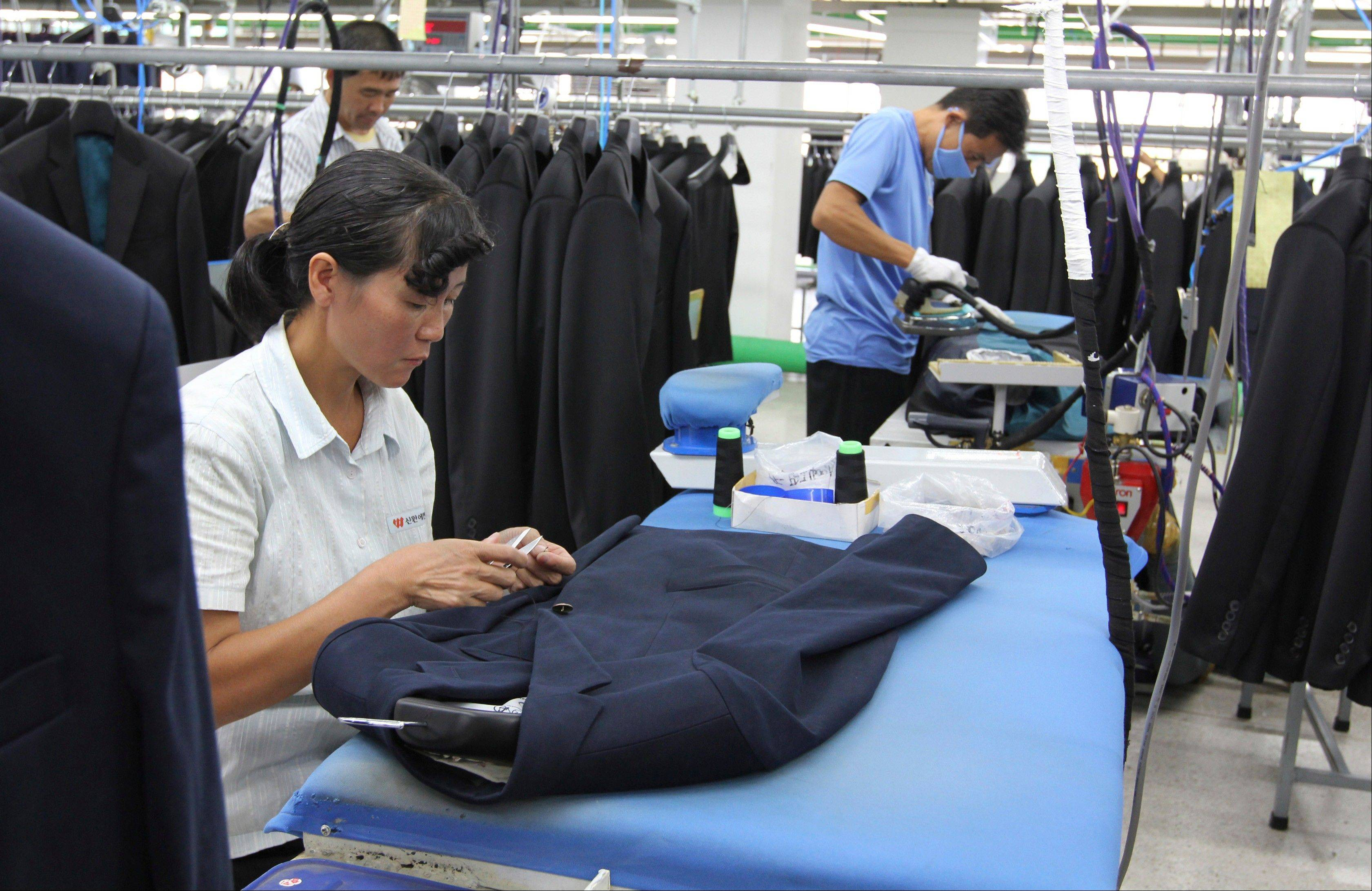 A North Korean woman sews a button on a suit at a factory in Kaesong, North Korea, run by ShinWon, a South Korean clothing maker. A few hundred South Korean managers, some wandering among quiet assembly lines, were all that remained Tuesday at the massive industrial park run by the rival Koreas after North Korea pulled its more than 50,000 workers from the complex.