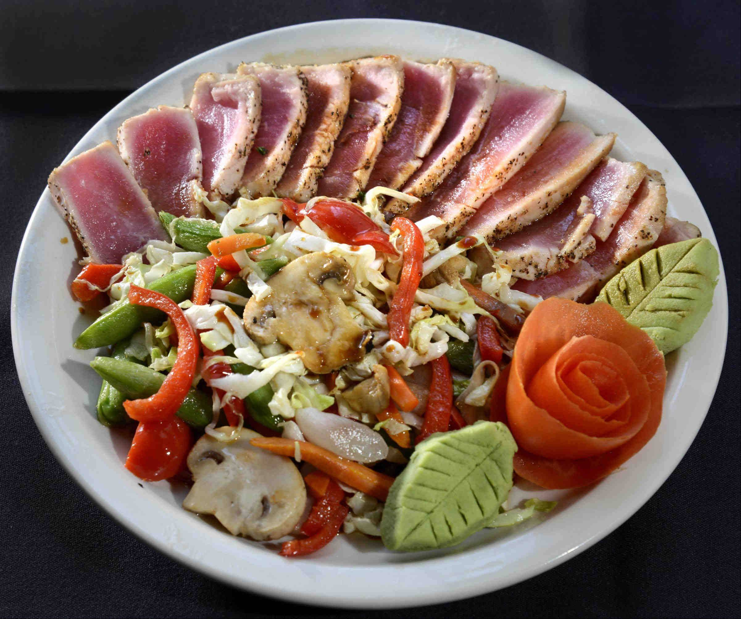 Ahi tuna with a rose cut tomato and wasabi sauce and vegetables is one of Pier 99 chef Edwon Montes' signature dishes.