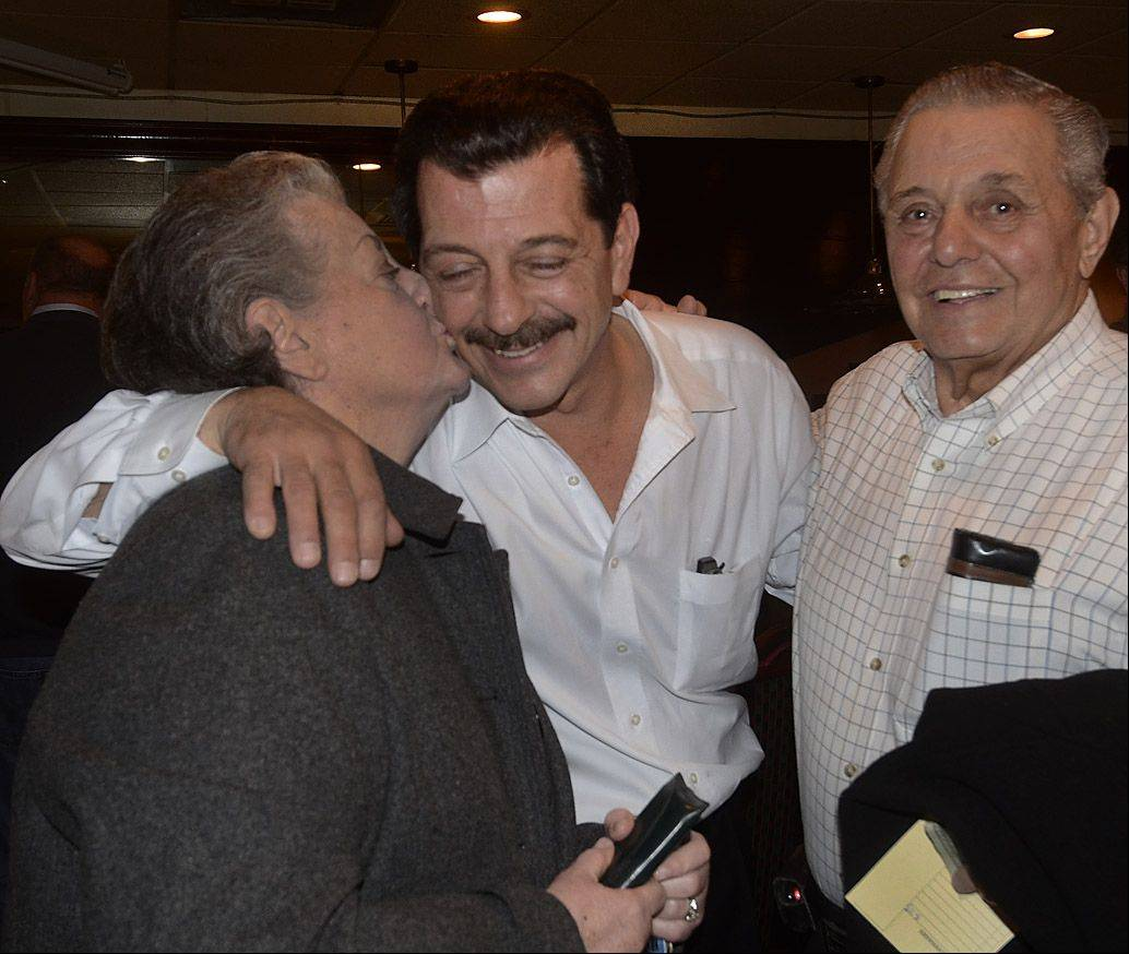 Dean Argiris is congratulated by his mother and father, Bertha and Sam Argiris, after winning the election for Wheeling village president.
