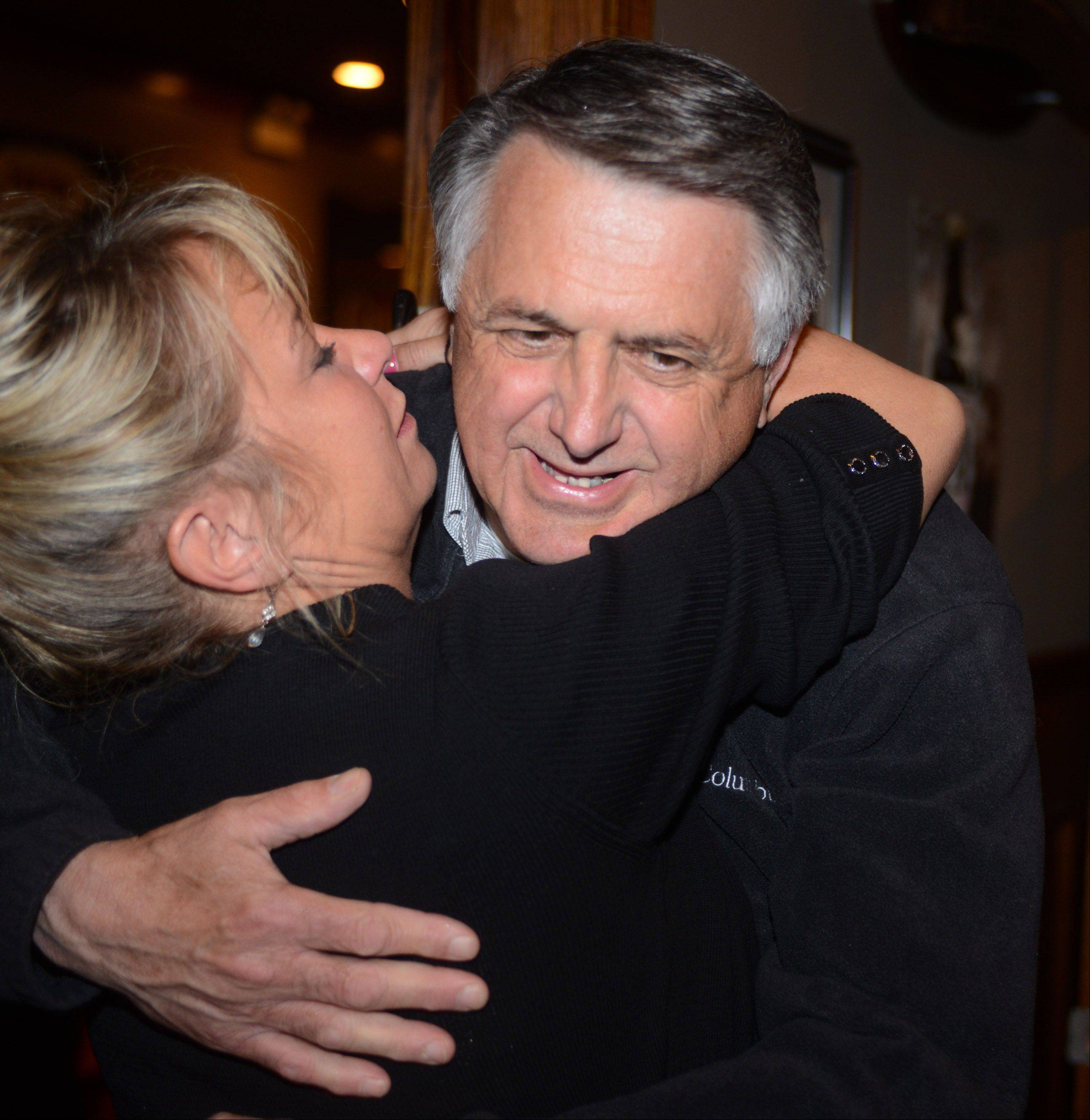 Island Lake mayor-elect Charles Amrich gets a hug from supporter Debra Jenkins Tuesday night at his victory party at Sideouts.