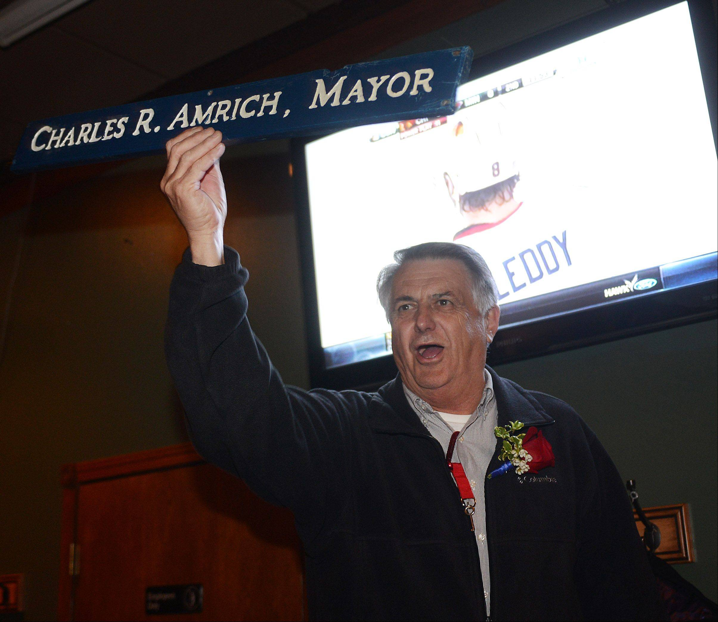 Paul Valade/pvalade@dailyherald.comIsland Lake mayoral candidate Charles Amrich celebrates at his victory party Tuesday night. He holds his 1985 mayor's sign from when he used to hold the office.