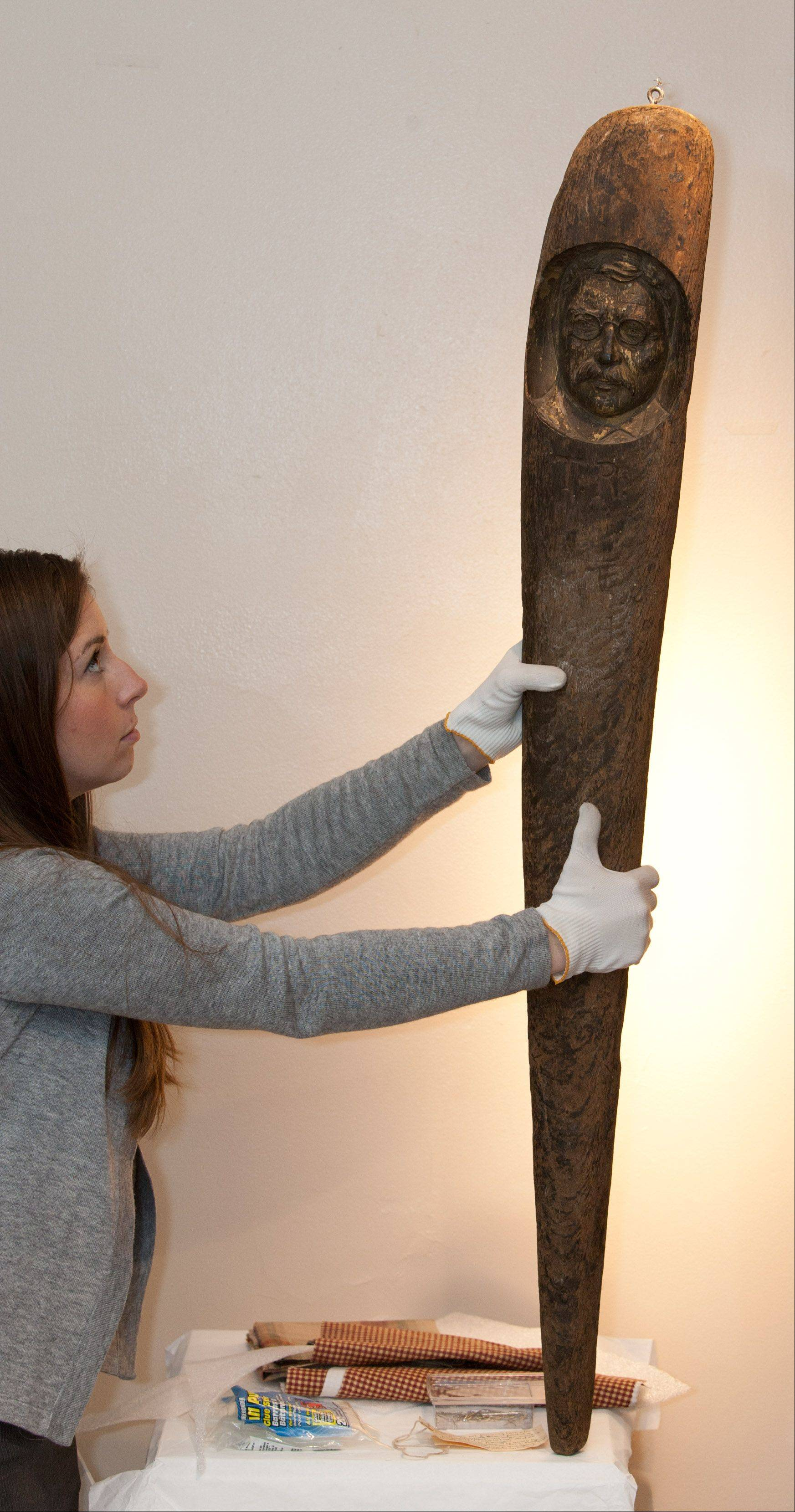 Museum curator Sara Arnas holds up a hand-carved Teddy Roosevelt walking stick on loan from the Aurora Historical Society. The walking stick commemorates Roosevelt's visit to Aurora and is an example of folk art with a political theme.