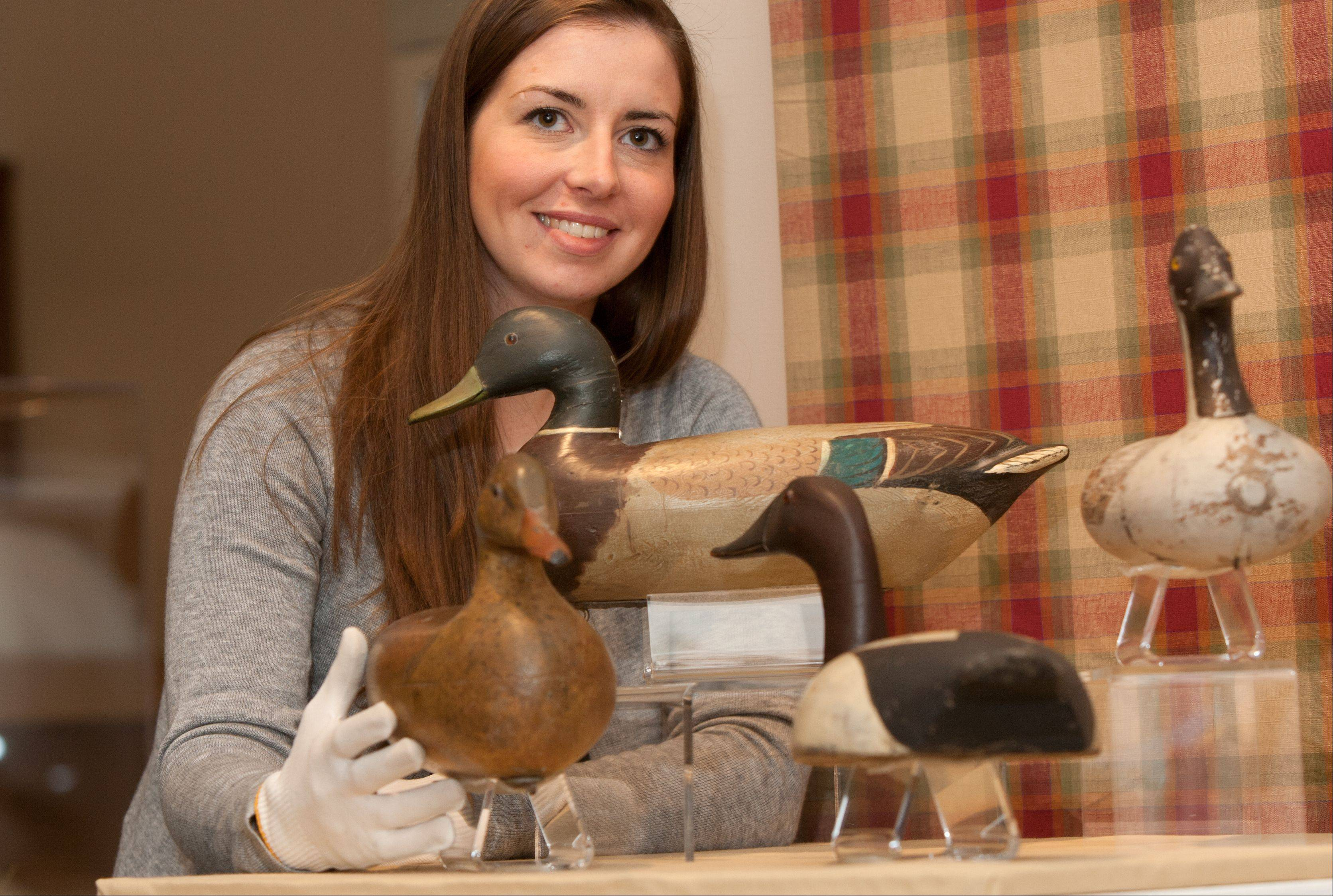 DuPage County Historical Museum Curator Sara Arnas shows hand-painted, hand-carved decoys that are part of the folk art exhibit. The decoys were used in duck hunting.
