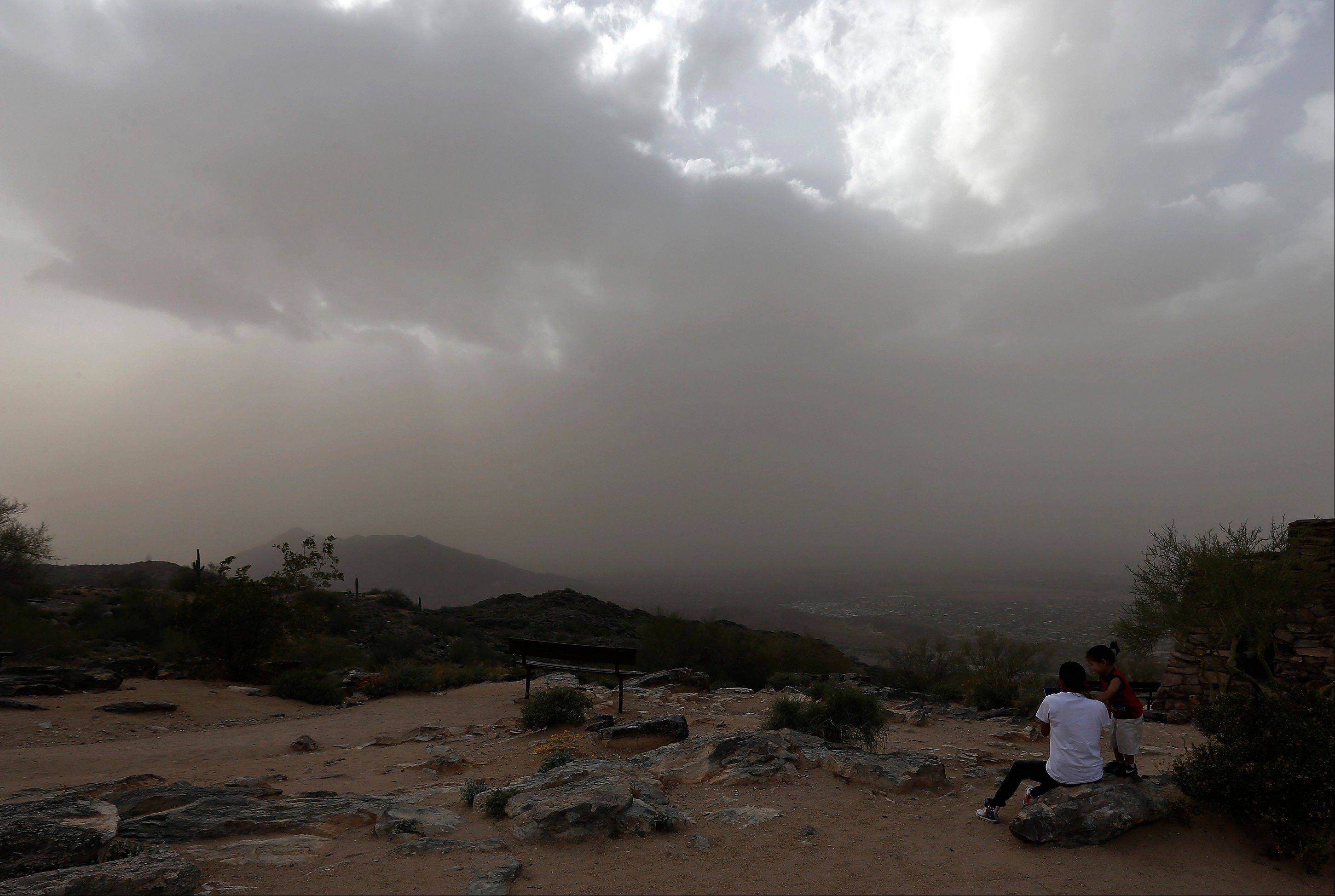 Tourists watch from the top of South Mountain as gusty winds envelop Phoenix in a dusty haze Monday, April 8, 2013.