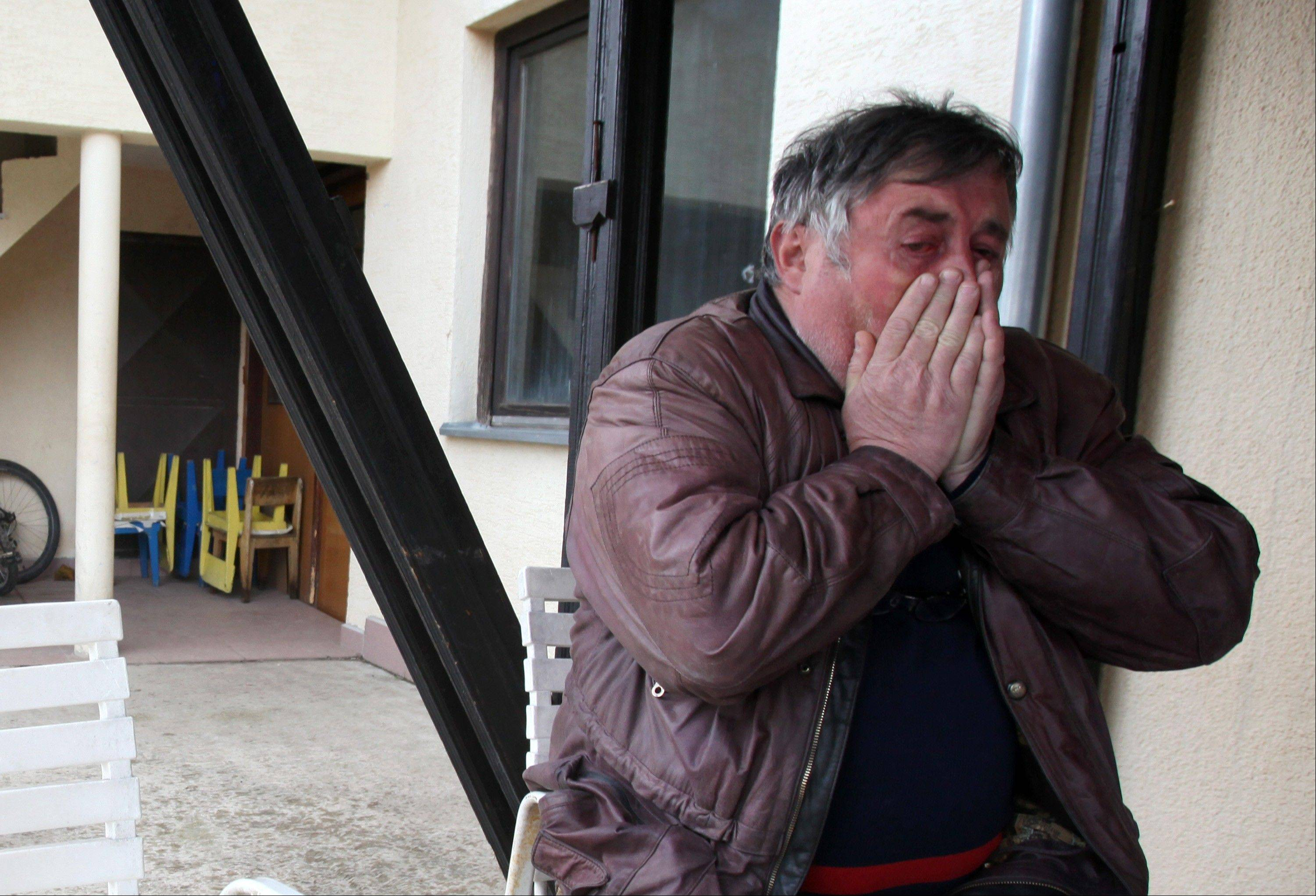 Radmilo Bogdanovic, brother of Ljubisa Bogdanovic cries in village of Velika Ivanca, Serbia, Tuesday, April 9, 2013. Ljubisa Bogdanovic a 60-year-old man gunned down 13 people, including a baby, in a house-to-house rampage in a quiet village on Tuesday before trying to kill himself and his wife, police and hospital officials said. Belgrade emergency hospital spokeswoman Nada Macura said the man, identified as Ljubisa Bogdanovic, used a handgun in the shooting spree at five houses. The dead included six women.