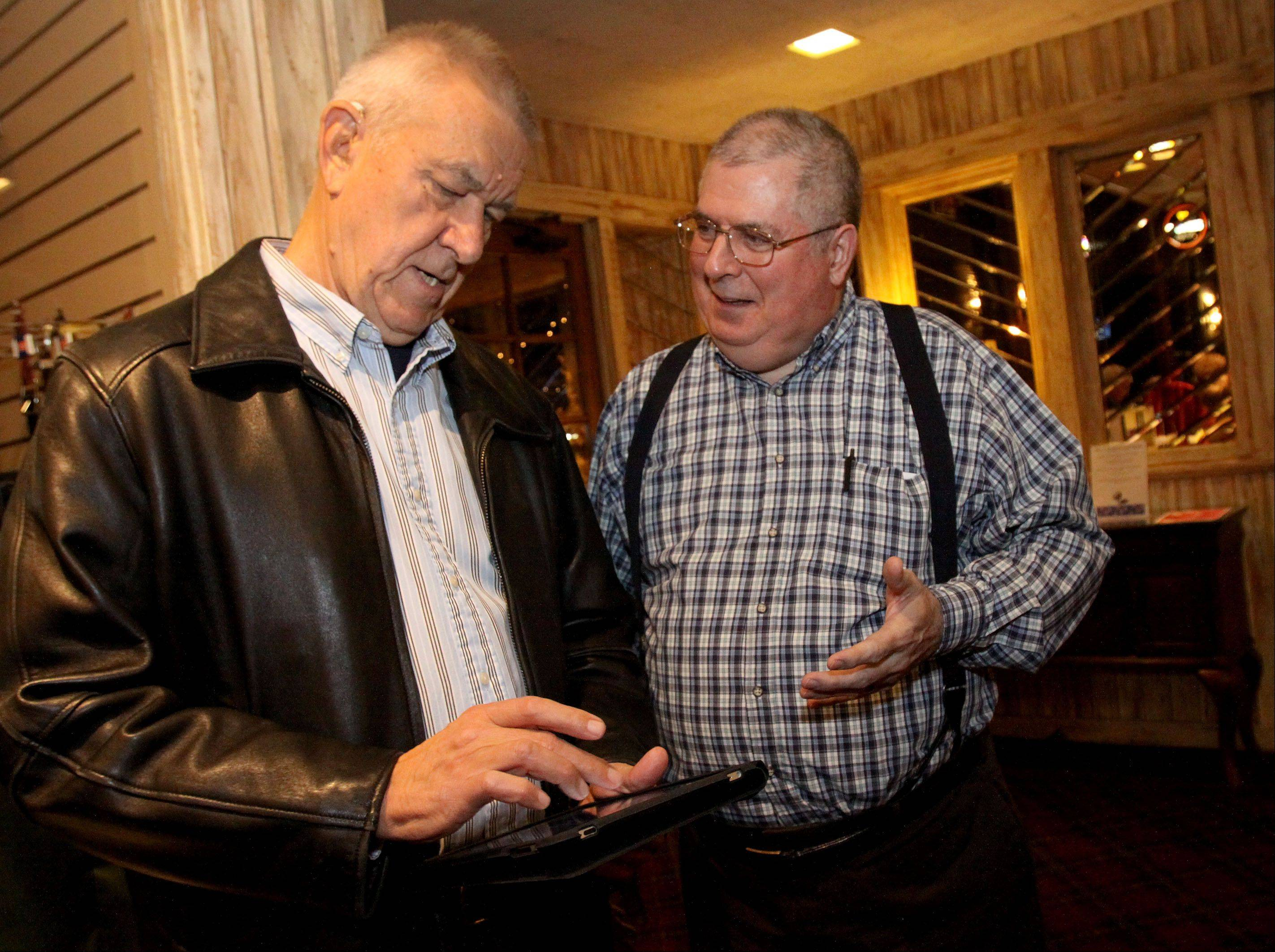 Wayne Woodward, mayoral candidate for West Chicago, right, looks for early results with Ed Petka, left, on Tuesday in West Chicago.
