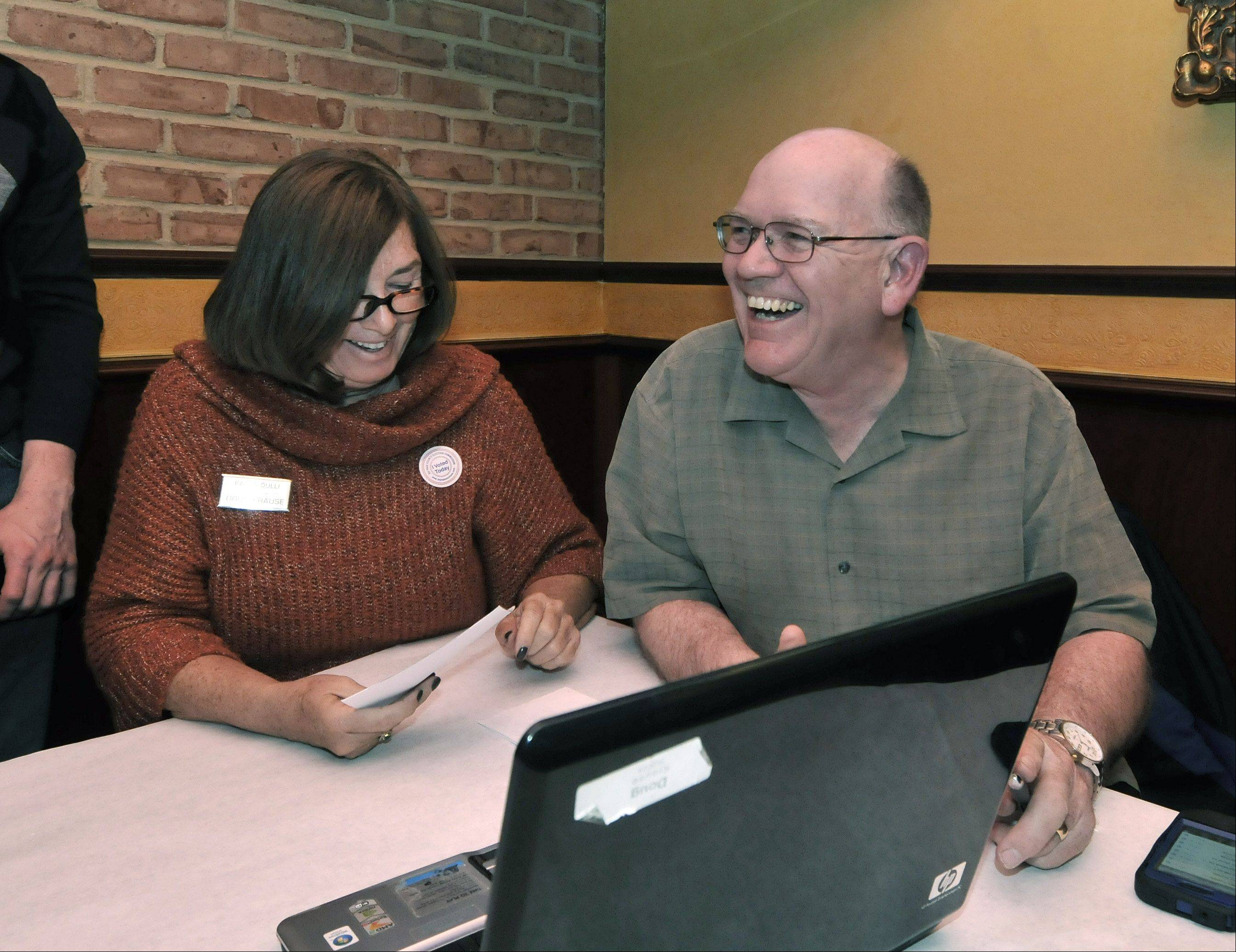 Doug Krause was all smiles Tuesday night as the early vote totals come in. He was monitoring the vote totals for the Naperville City Council Tuesday night with family and friends, and supporters including his campaign manager Paula Dulli, left, at Traversos restaurant in Naperville. He's the longest serving Naperville City Council member and is running for re-election.
