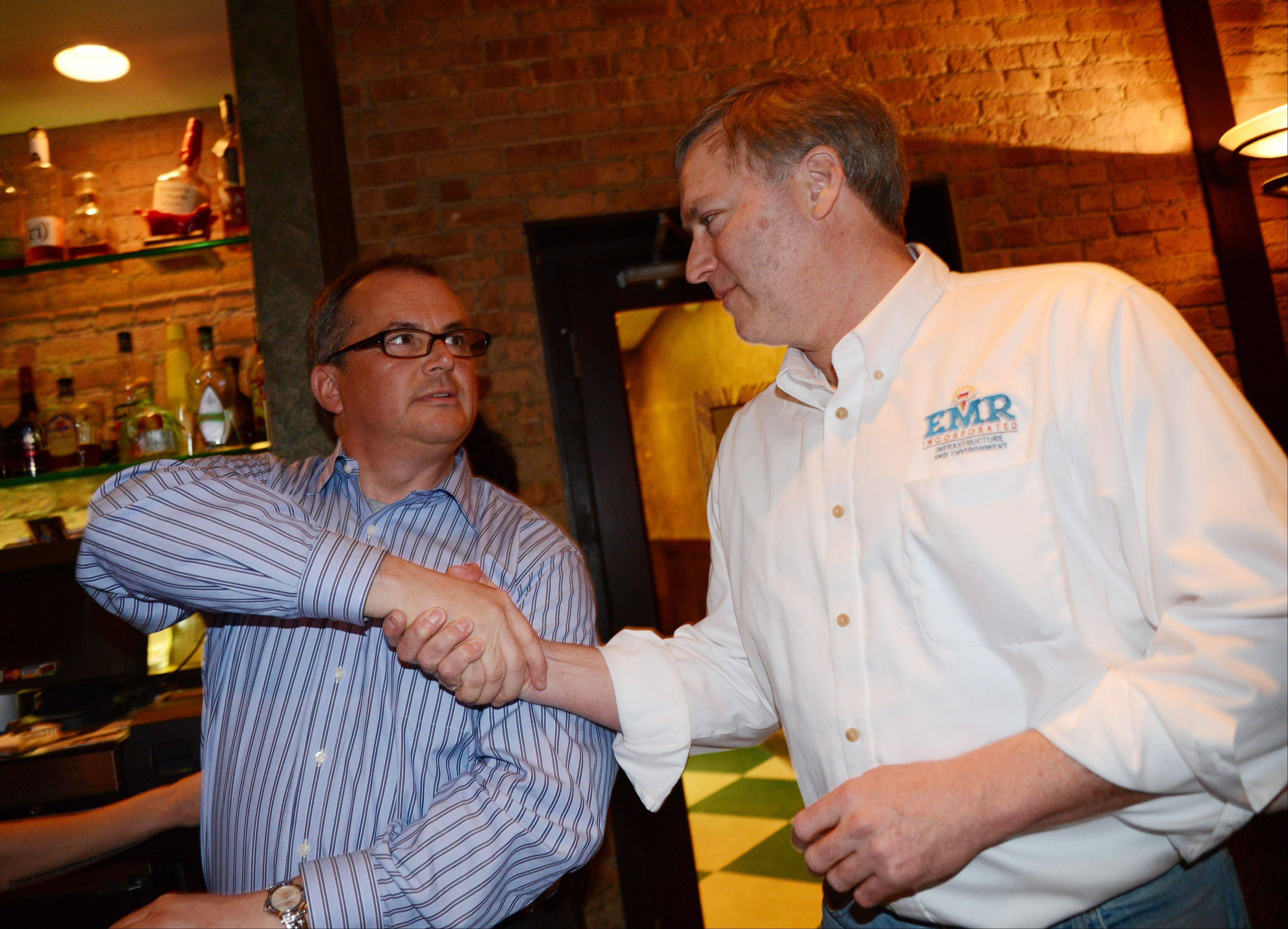 Rob Hanlon,left, one of the two candidates for Winfield village president, gets a hand shake from Jay Olsen on Tuesday. Hanlon lost to Erik Spande.