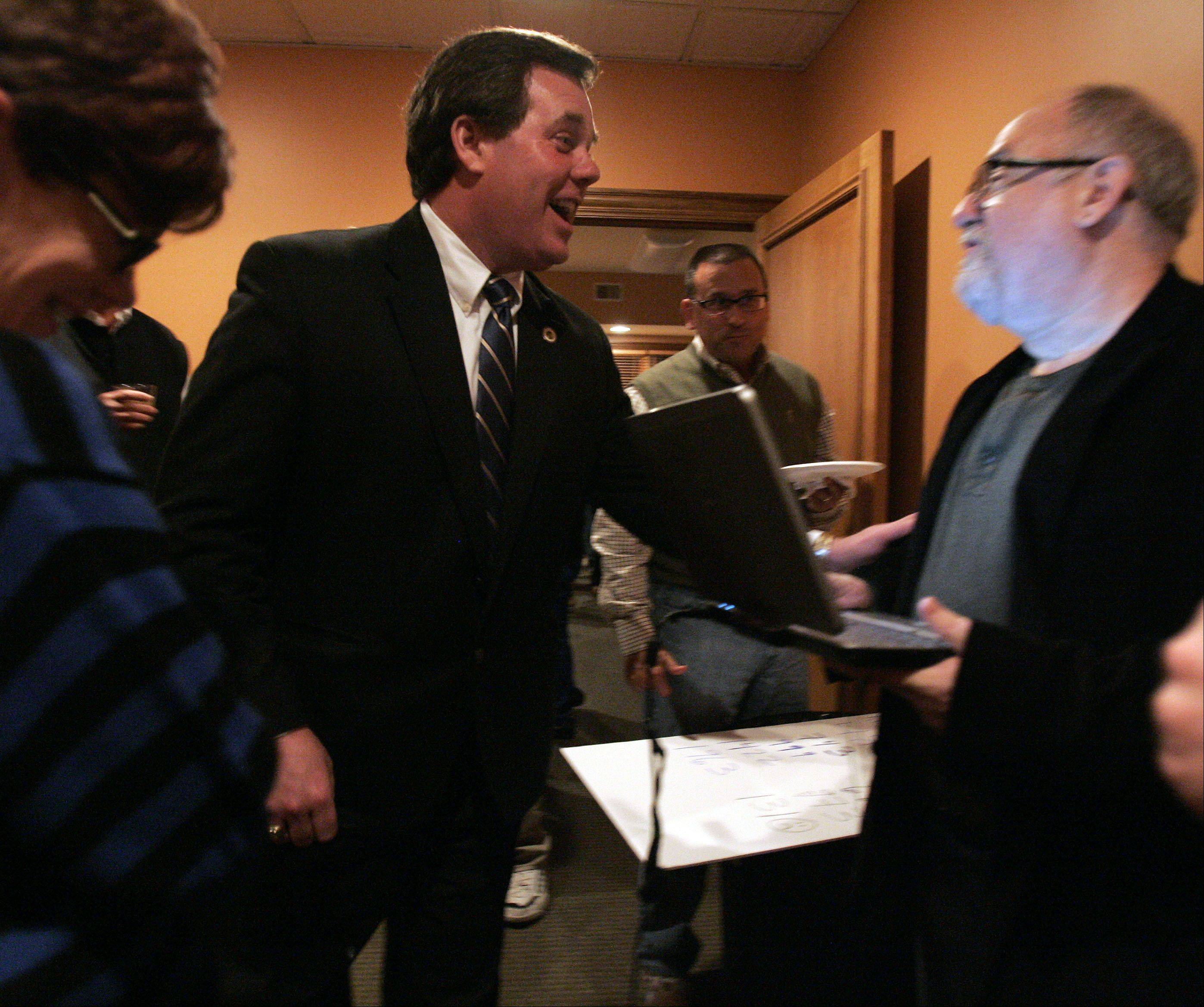 Geneva mayor Kevin Burns checks results with Joe Stanton at Burns' office in Geneva Tuesday.