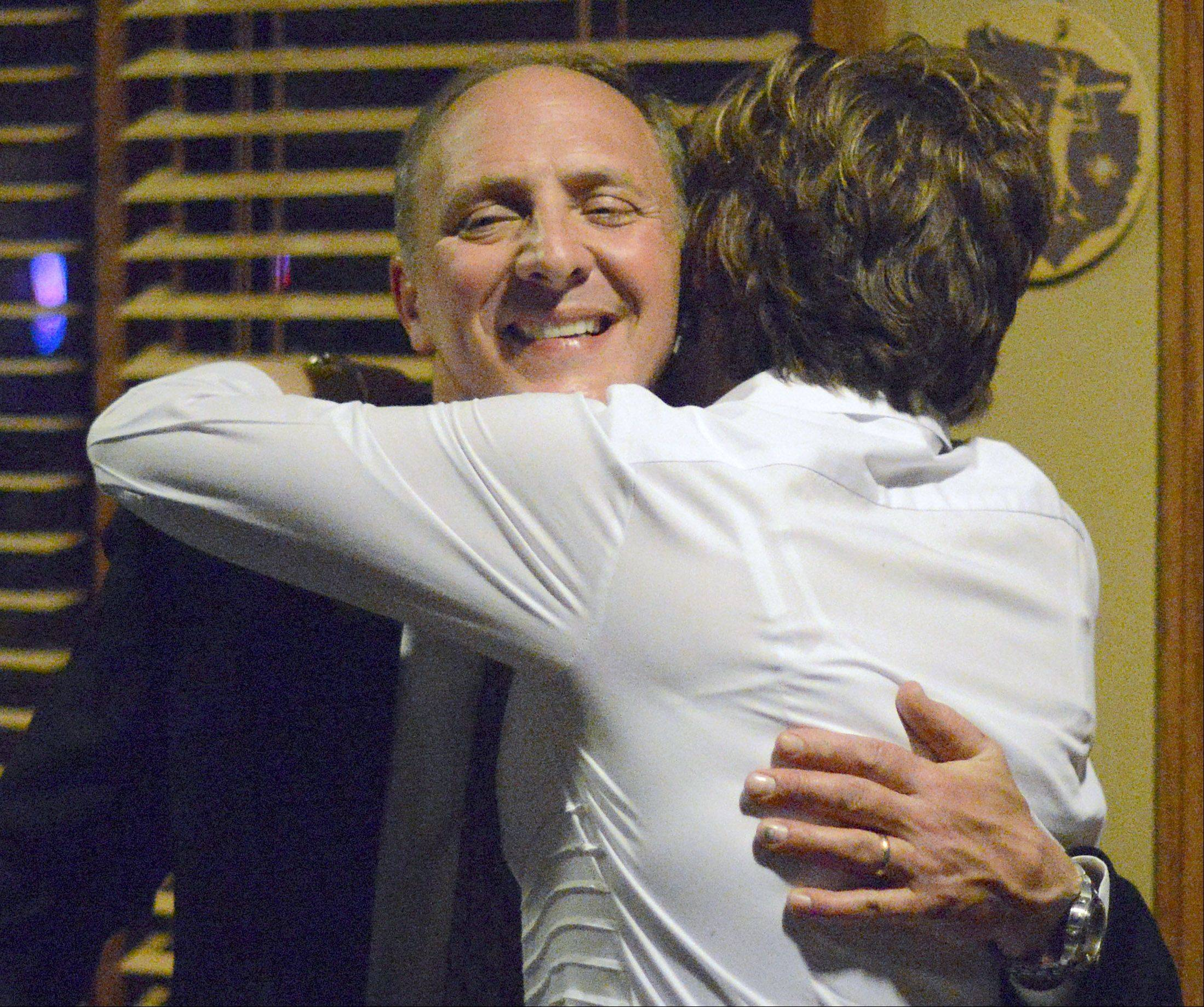 Sugar Grove President Sean Michels gets a congratulatory hug from his wife, Val, after the final results arrive at his election night party at the Open Range Southwest Grill in Sugar Grove.