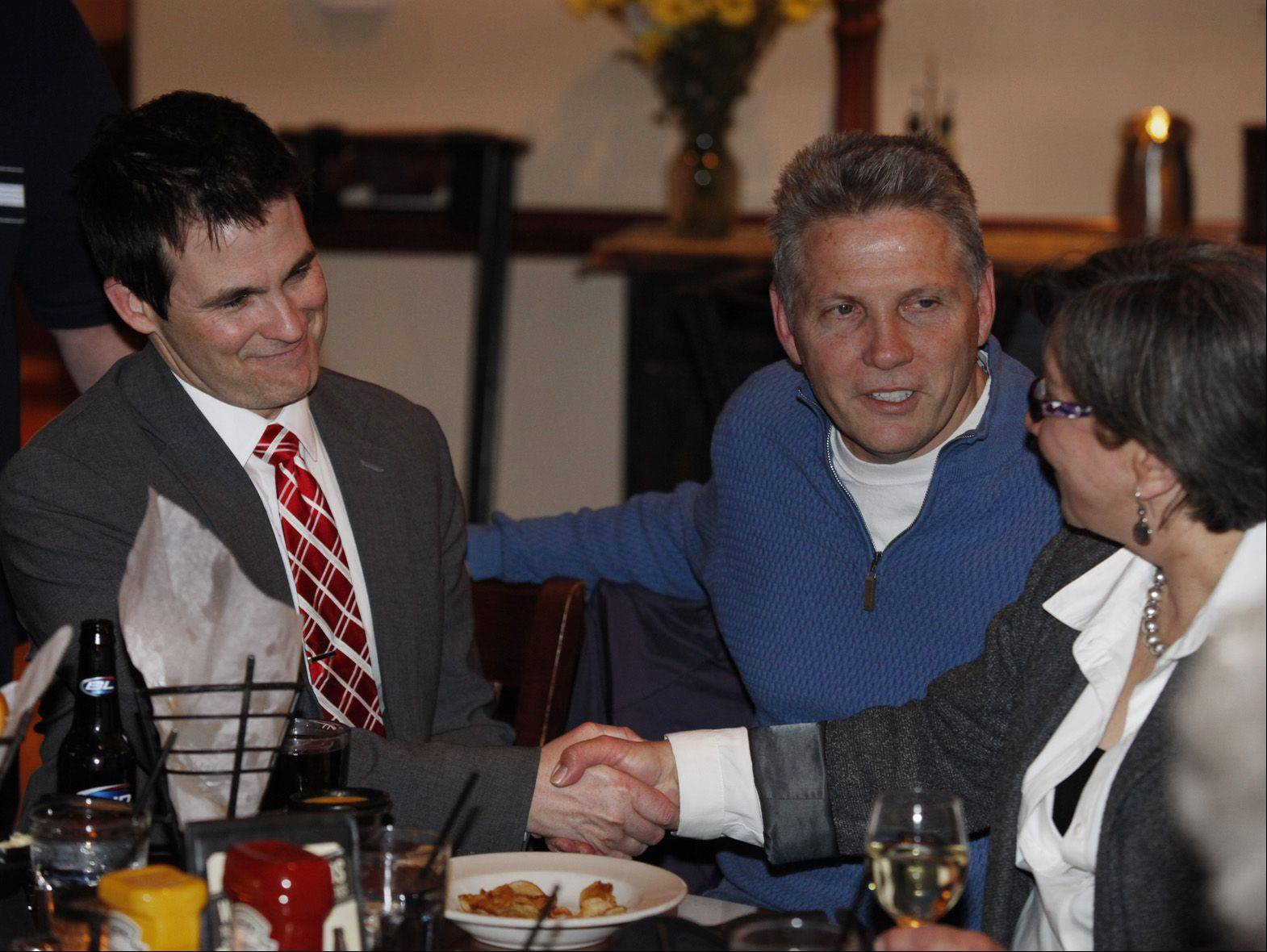 Chris Nelson, left, shakes the hand of supporter Cheryl Anderley, far right, Tuesday night at Emmett's Tavern and Brewing Company in West Dundee. At center is Nelson's campaign manager Don Rage. Nelson was elected as West Dundee village president.