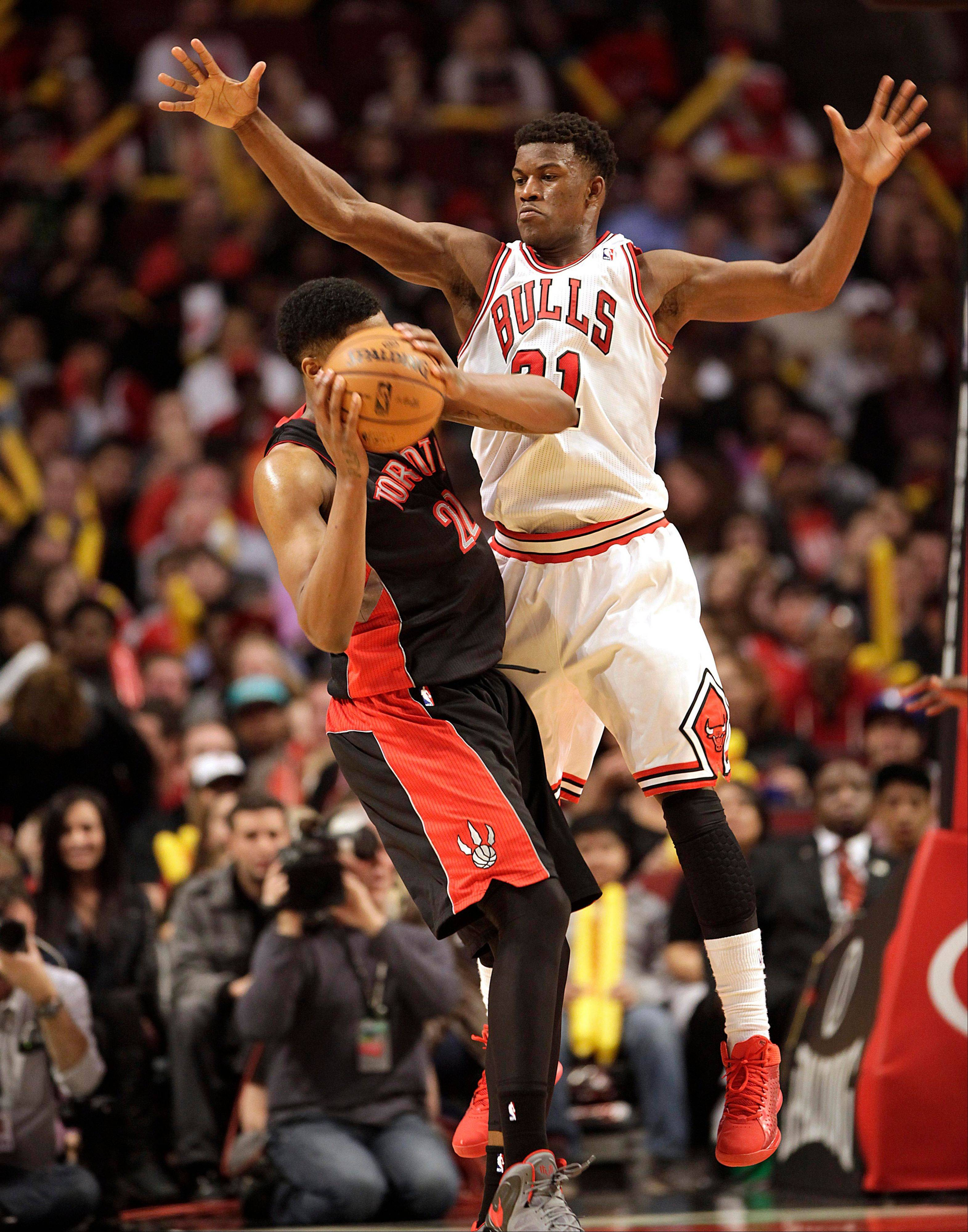 Chicago Bulls' Jimmy Butler plays defense against the Toronto Raptors' Rudy Gay during the second half as the Raptors beat the Bulls 101-98 in an NBA basketball game on Tuesday, April 9, 2013 in Chicago.