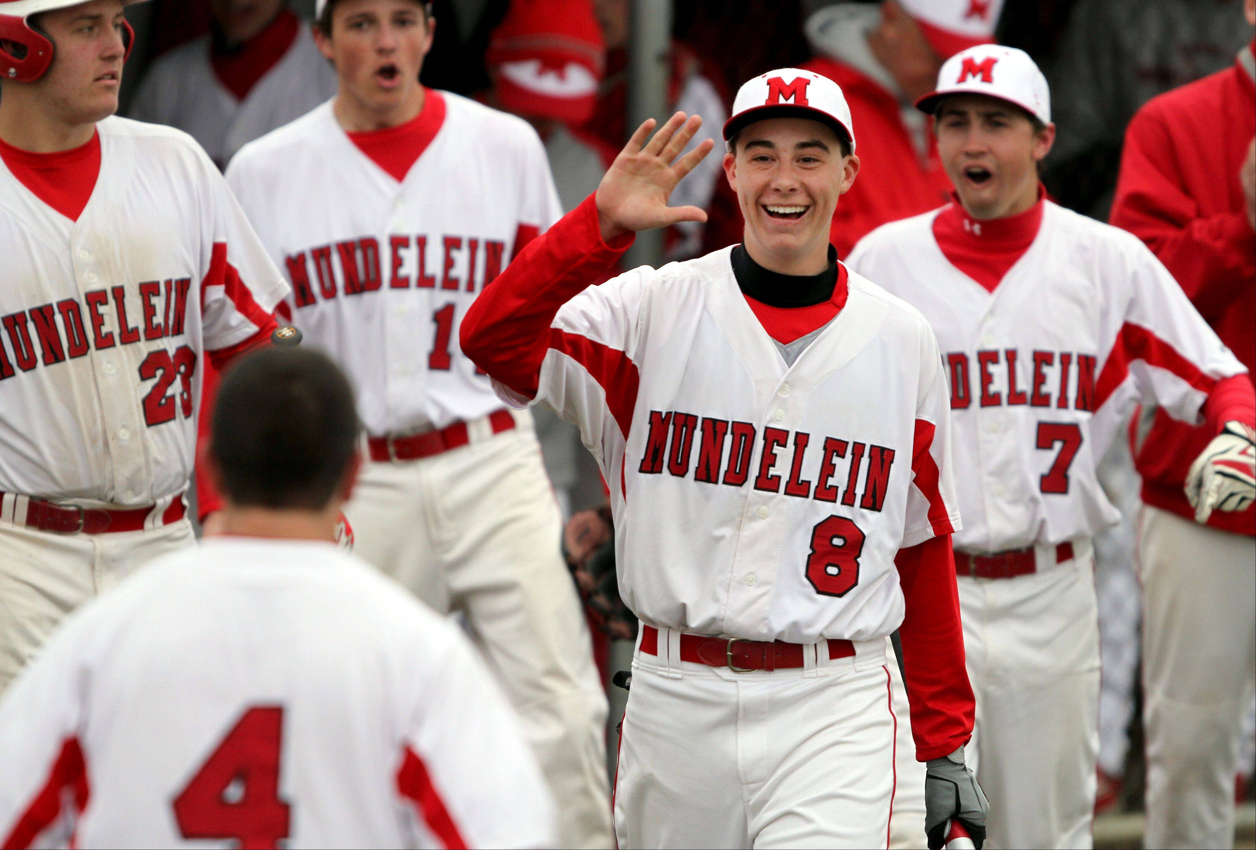 Mundelein's Derek Parola, right, goes to high-five teammate Thomas Gandolfi after Gandolfi scored in the third inning against Lake Zurich on Tuesday at Mundelein.