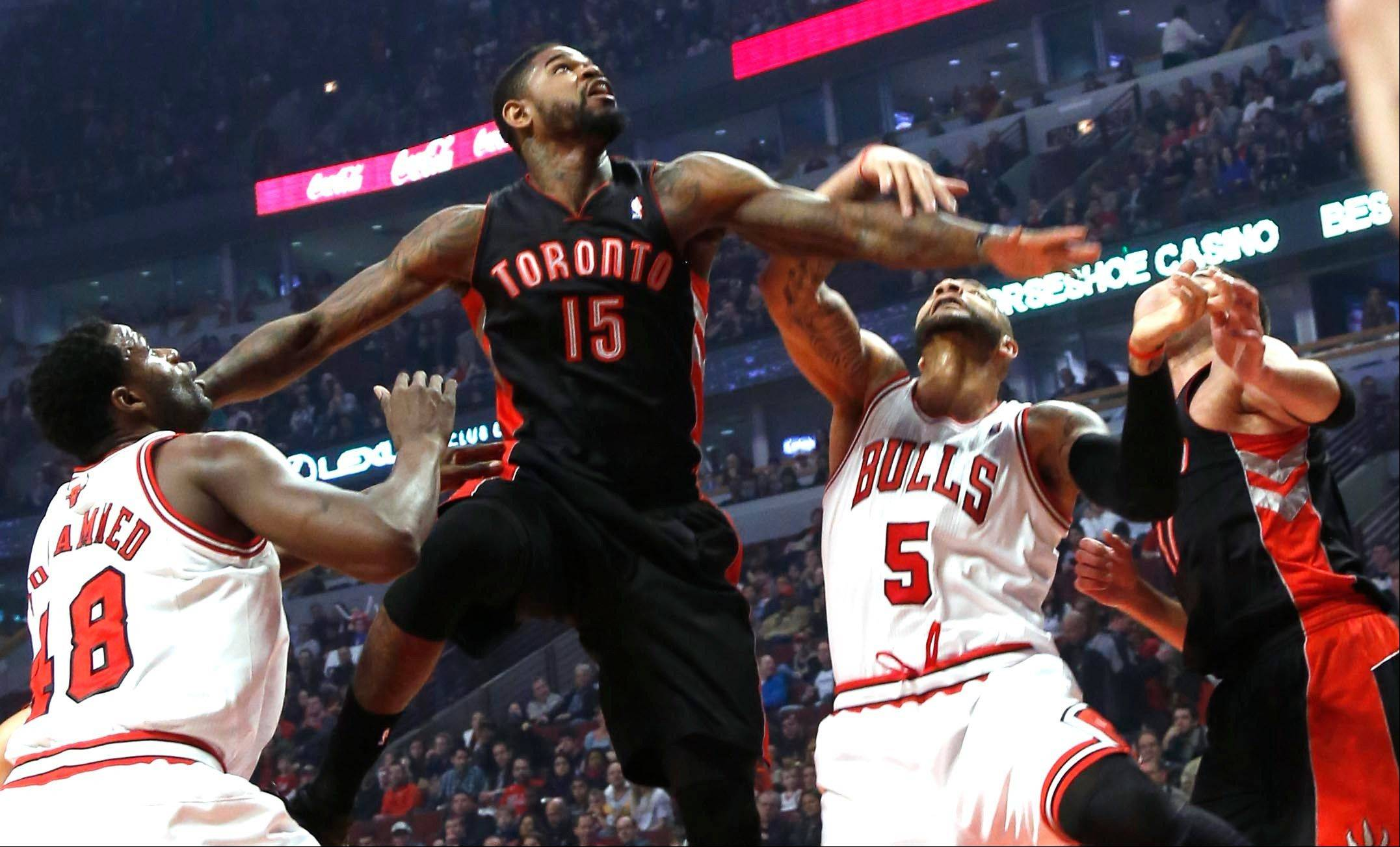 Toronto's Amir Johnson leaps above Chicago Bulls players Nazr Mohammed and Carlos Boozer trying to get a rebound during the first quarter in an NBA basketball game on Tuesday, April 9, 2013 in Chicago.
