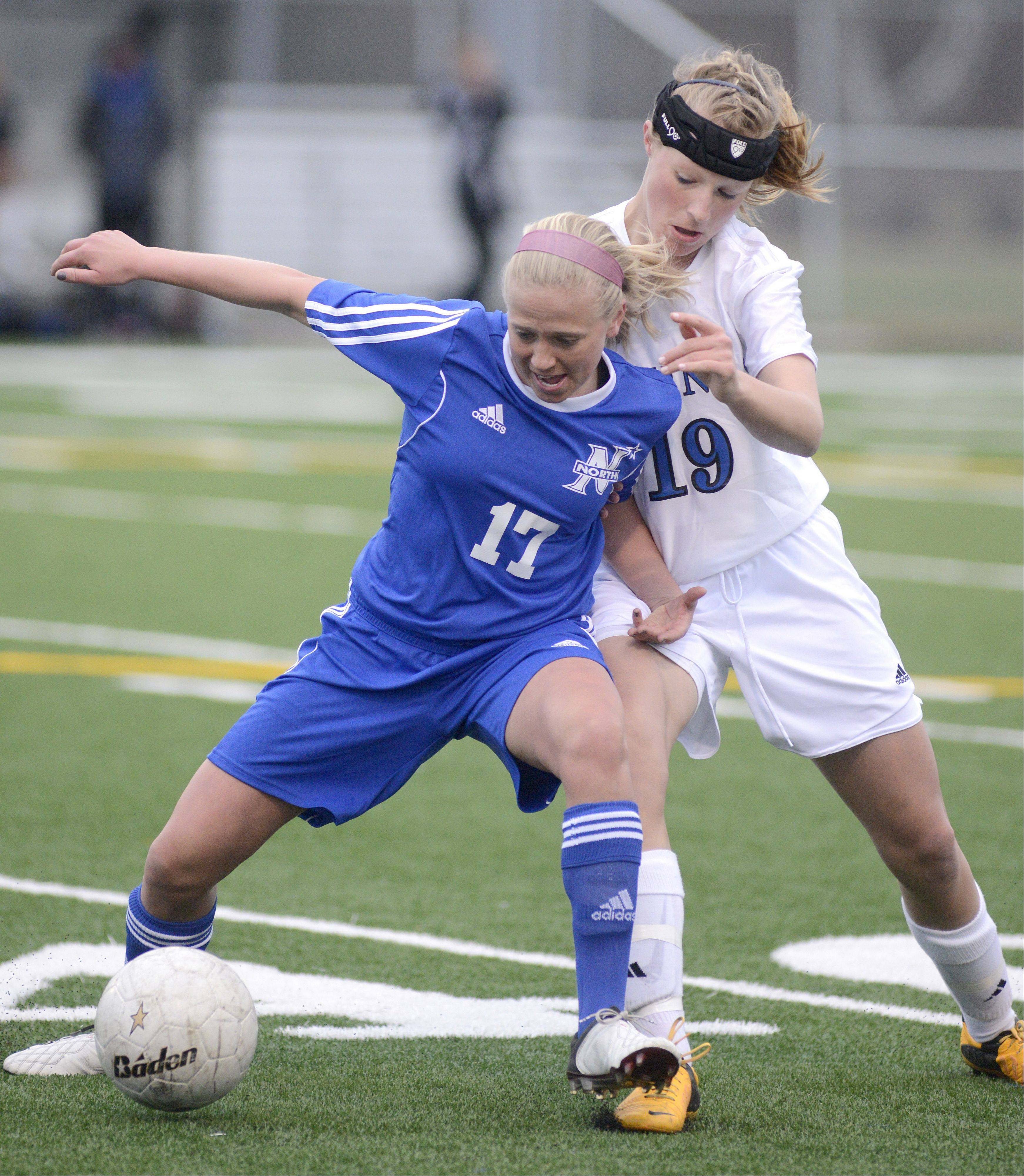 St. Charles North's Kelly Manski and Geneva's Megan Kozlow battle for the ball in the first half on Tuesday, April 9.