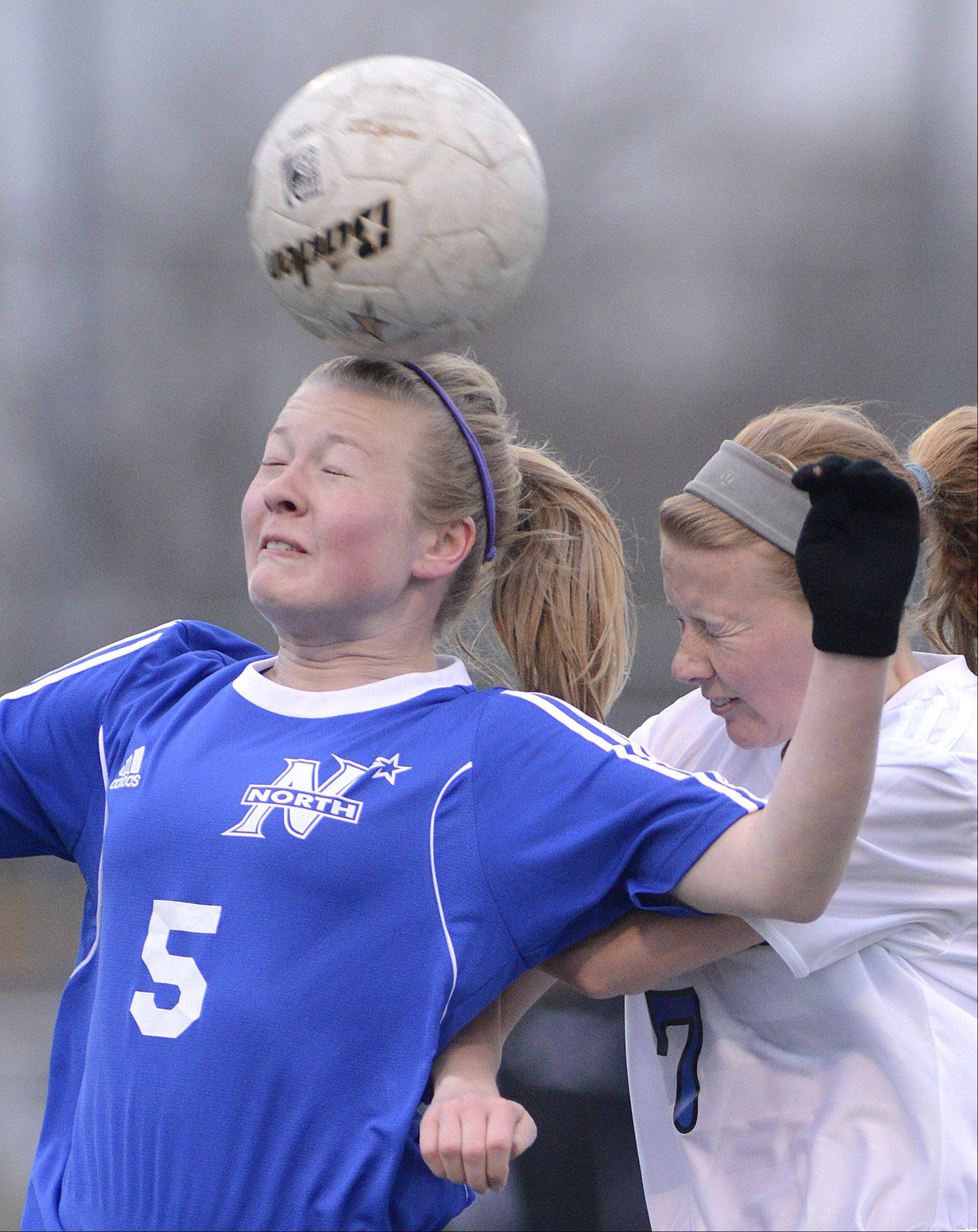St. Charles North's Natalie Winkates heads the ball before Geneva's Hope Goodman can get to it in the first half on Tuesday, April 9.
