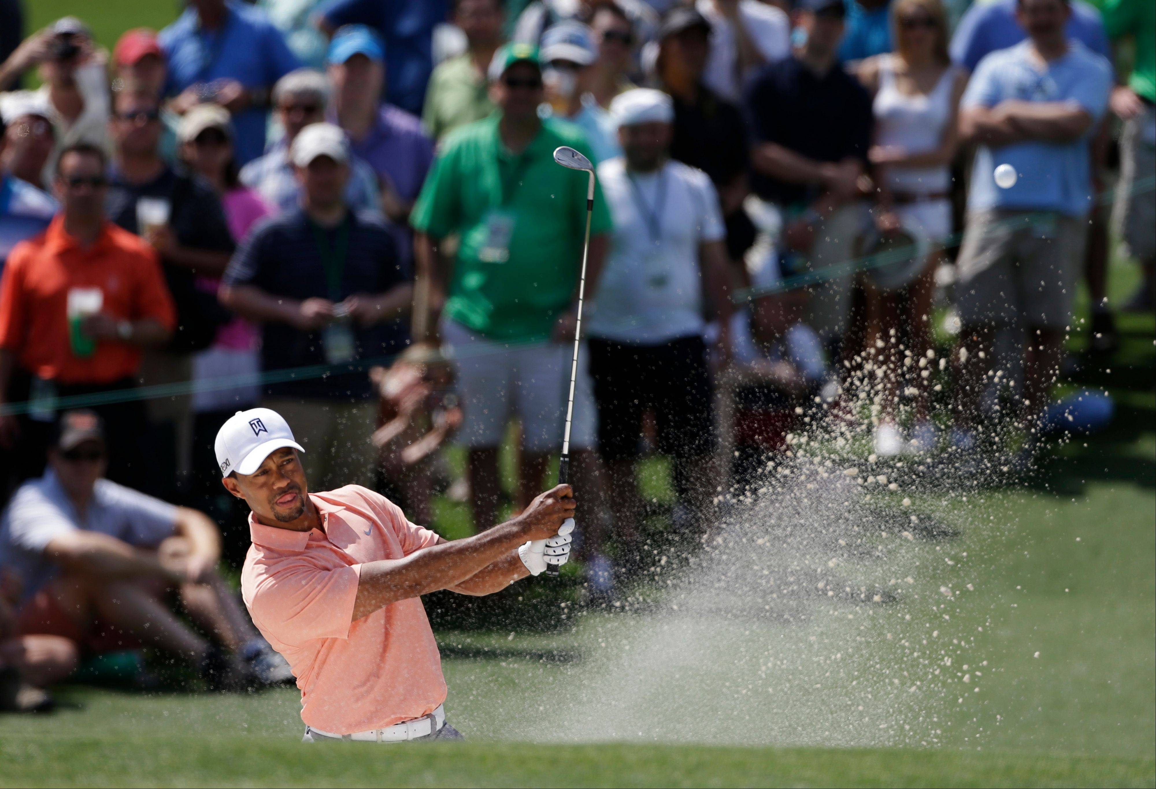 Tiger Woods watches his shot out of a bunker on the second hole during a practice round for the Masters golf tournament Tuesday, April 9, 2013, in Augusta, Ga.