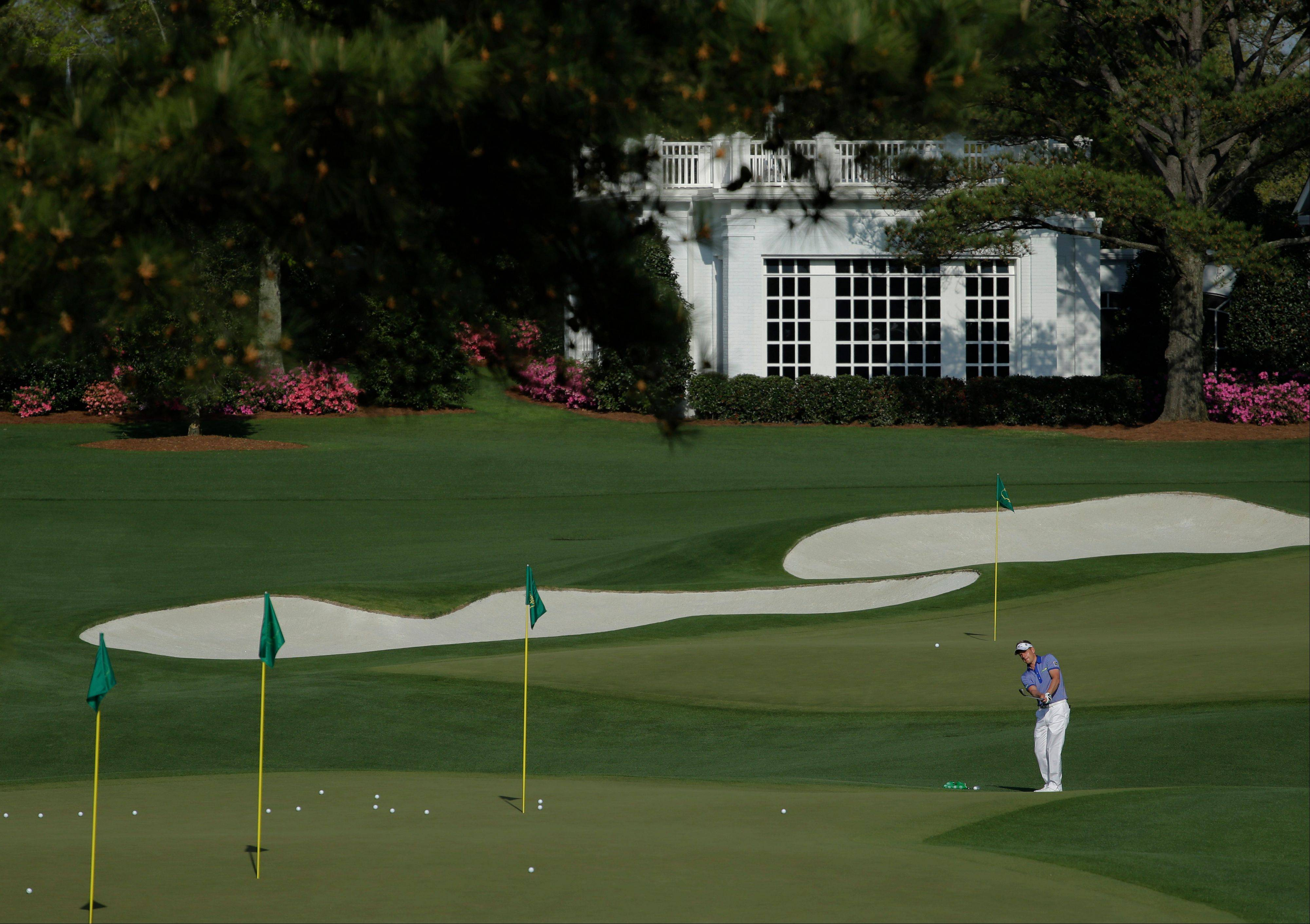 Luke Donald, a Northwestern grad from England, chips on the driving range during a practice round for the Masters golf tournament Tuesday in Augusta, Ga.