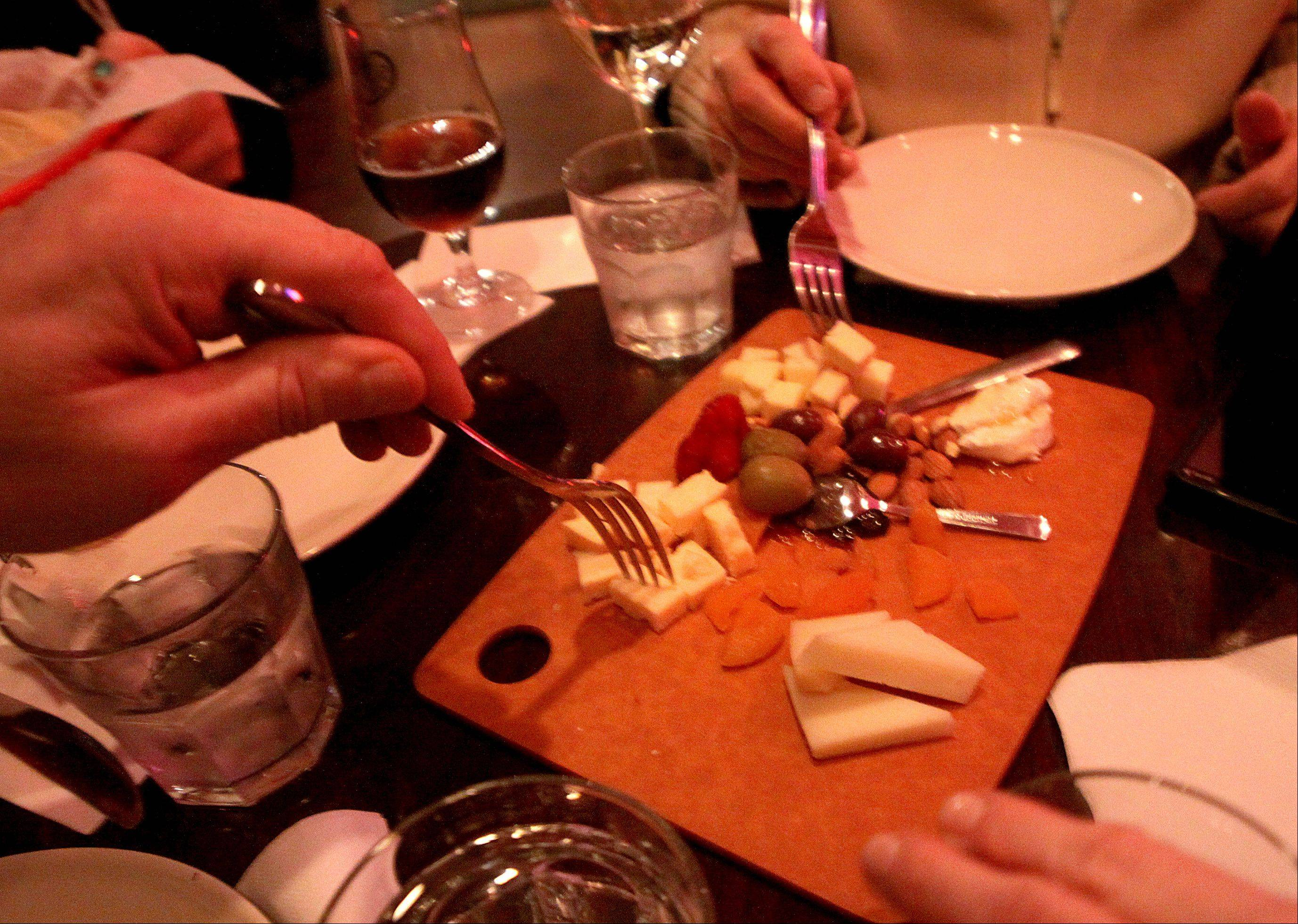 Patrons enjoy a plate of olives, cheese and dried fruit at the Tuscan Market Wine Bar in Arlington Heights.