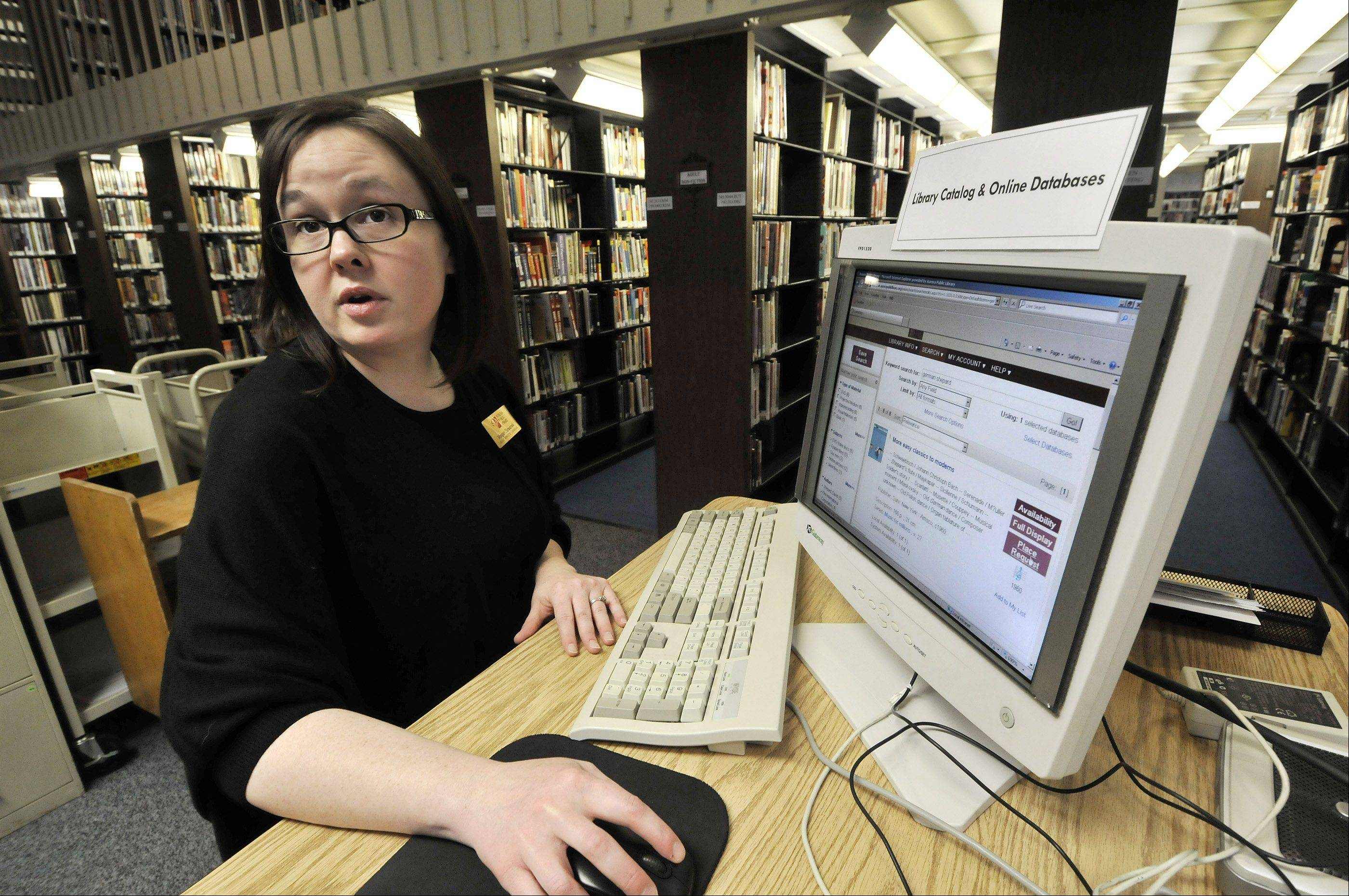 Librarian Magan Szwarek explains the Aurora Public Library�s new online catalog, which began operation Thursday. Among other things, patrons can reserve books and audio books online and keep track of items they�ve read.