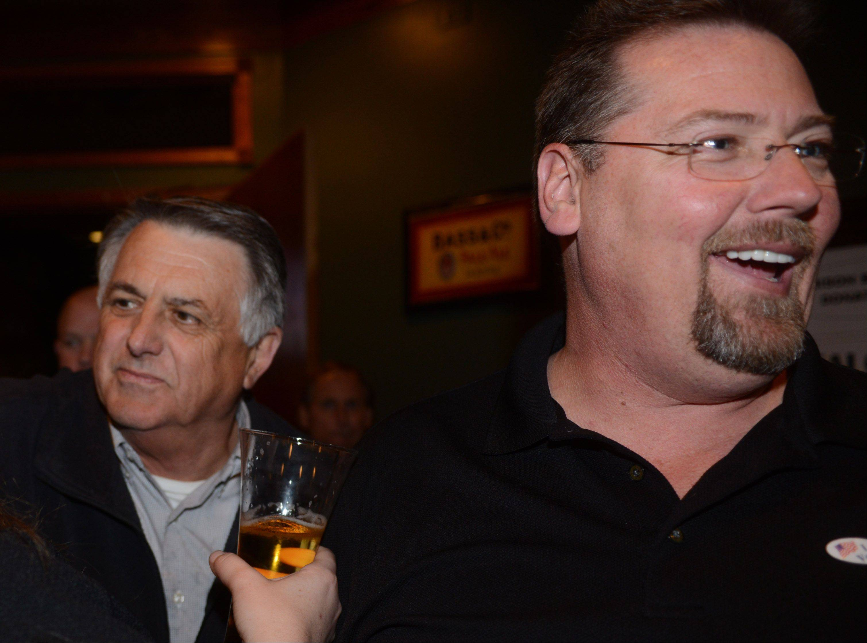 Charles Amrich, left, and Keith Johns are all smiles during their victory party Tuesday night in Island Lake.