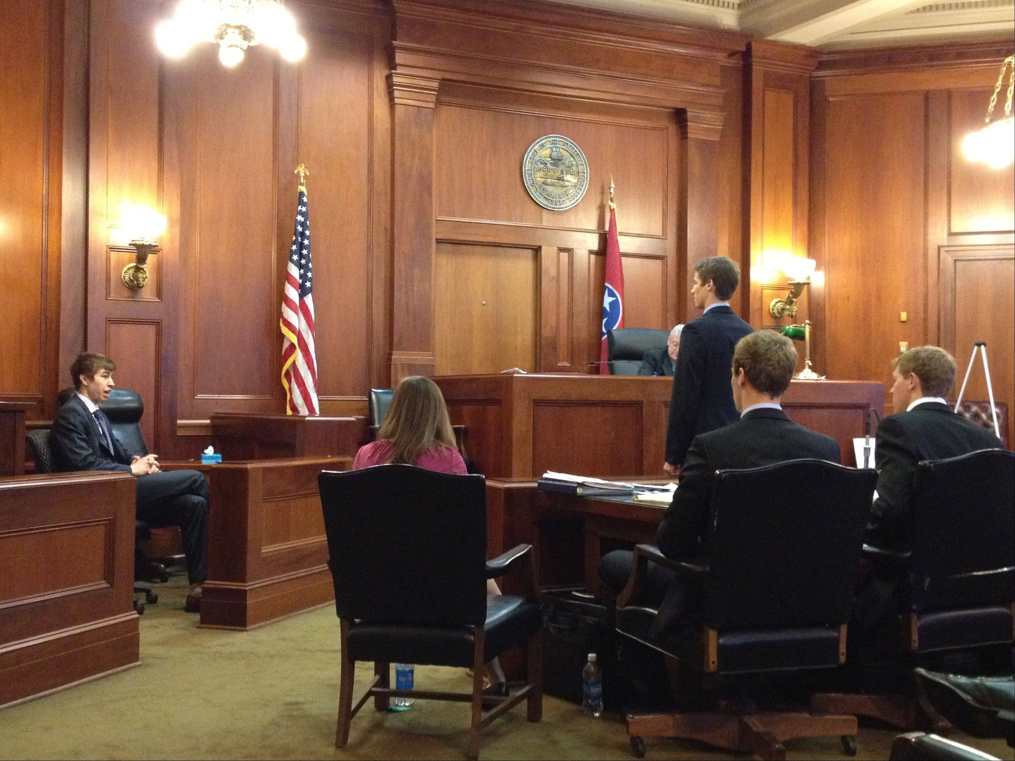 Wheaton College Mock Trial Team member John Patrick takes the witness stand last year at the American Mock Trial Association�s Opening Round Championship Series in Memphis, Tenn. Team Captain Trenton Van Oss is standing.