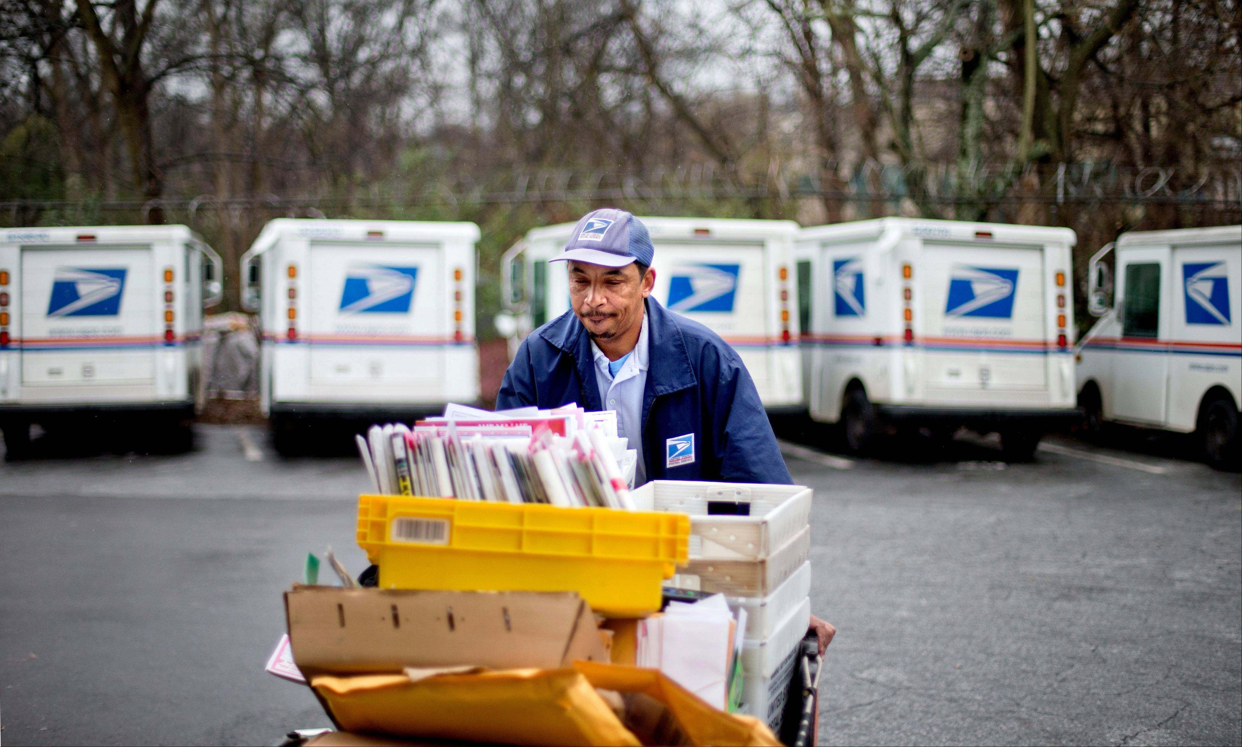 The U.S. Postal Service says it will delay plans to cut Saturday mail delivery because Congress isn't allowing the change.