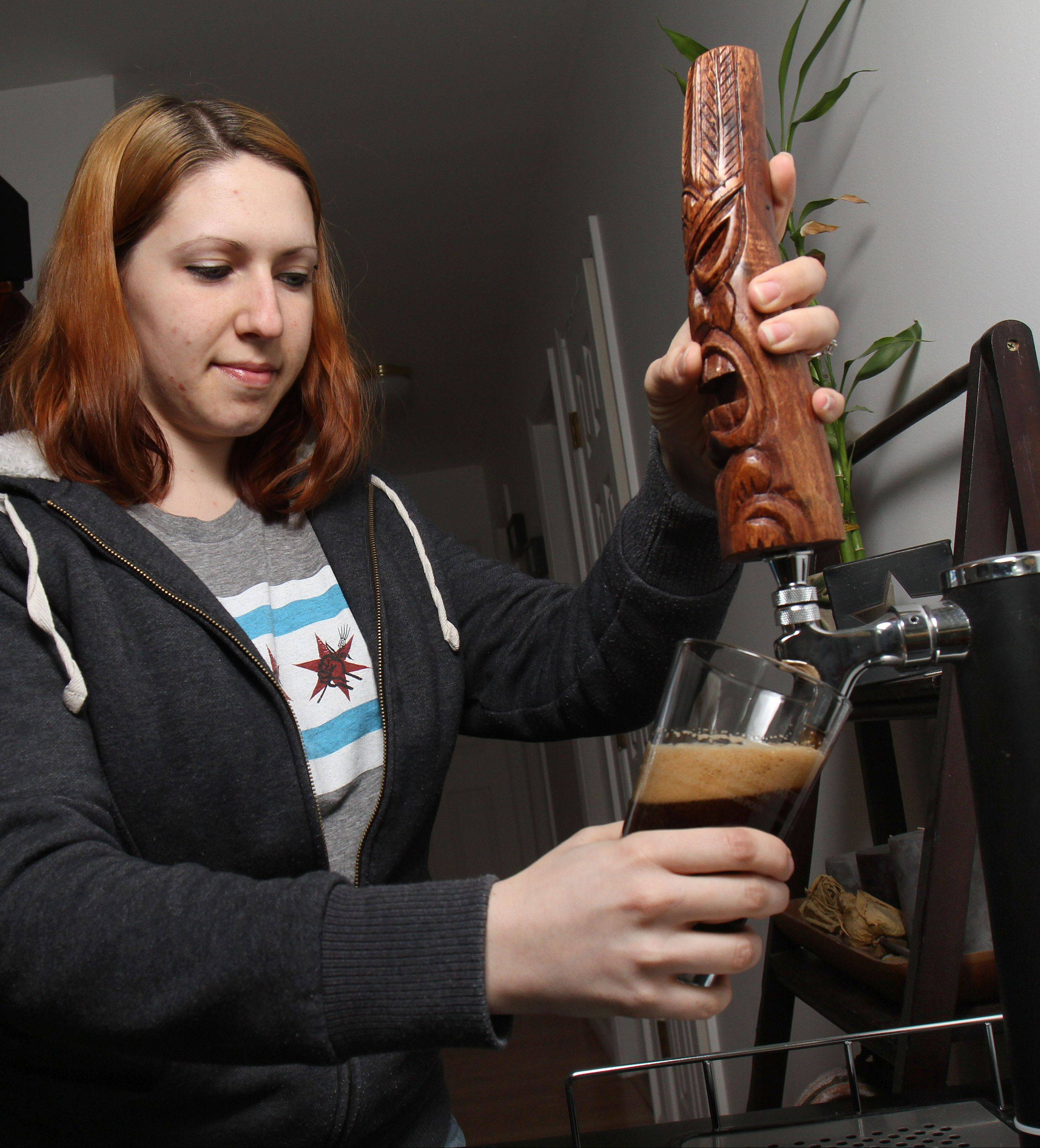Valerie Delligatti of Round Lake Beach pours a pint of stout she brewed at home. Delligatti belongs to the Babble Home brewing Club of Lake County.