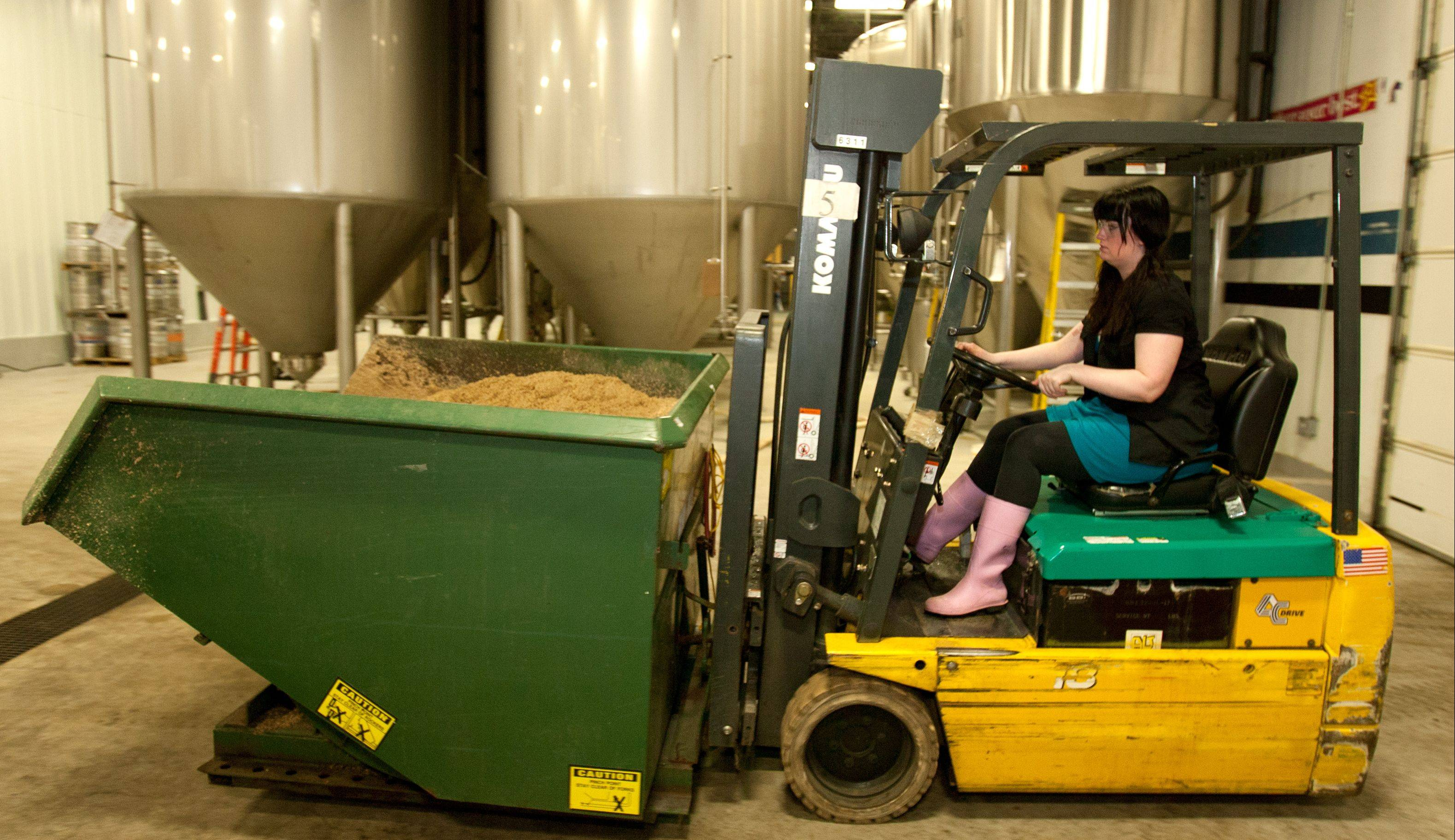 Ashleigh Arnold, brew master at the Two Brothers Brewery in Warrenville, moves spent grain within the factory.