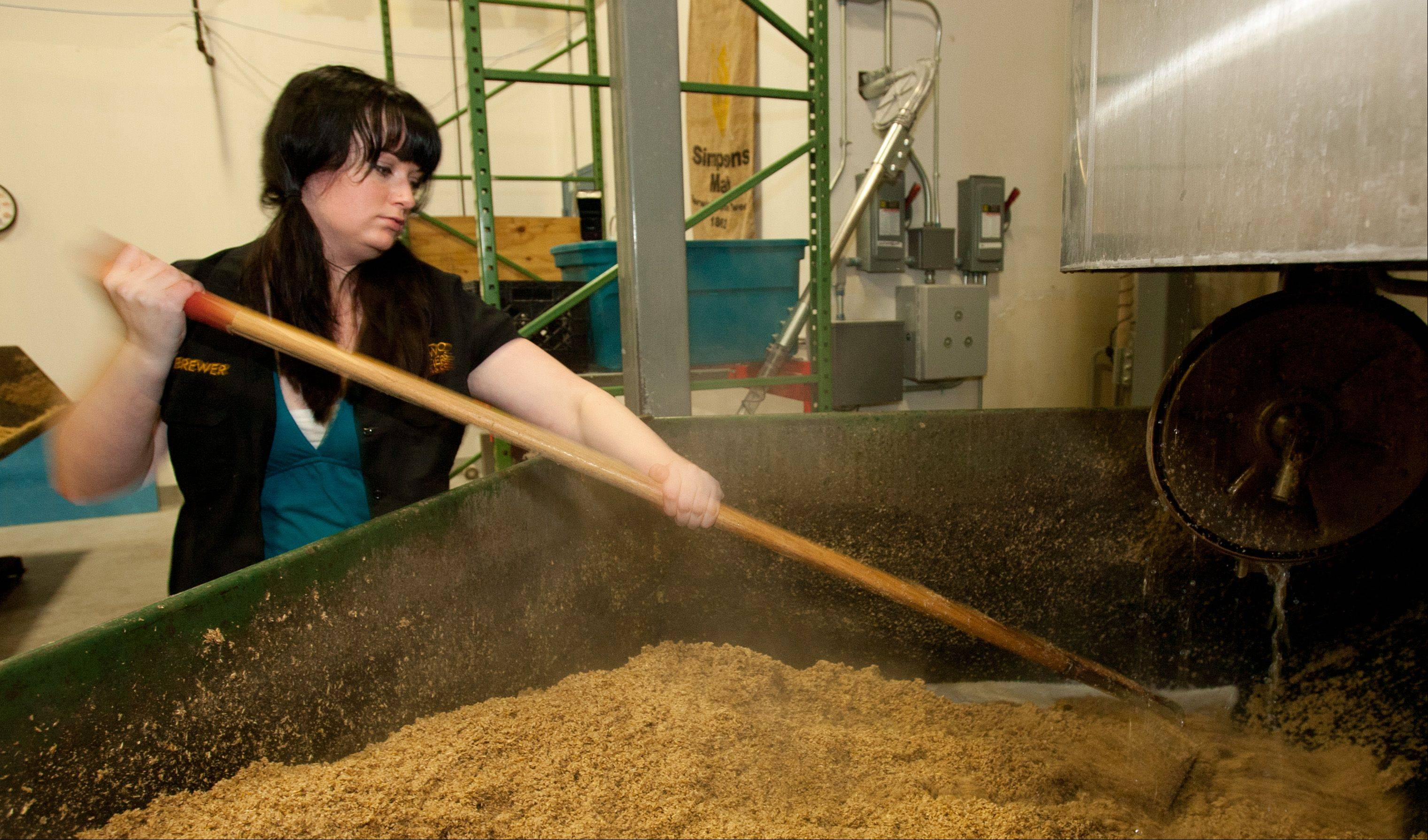 Ashleigh Arnold, brew master at the Two Brothers Brewery in Warrenville, stirs spent grain.